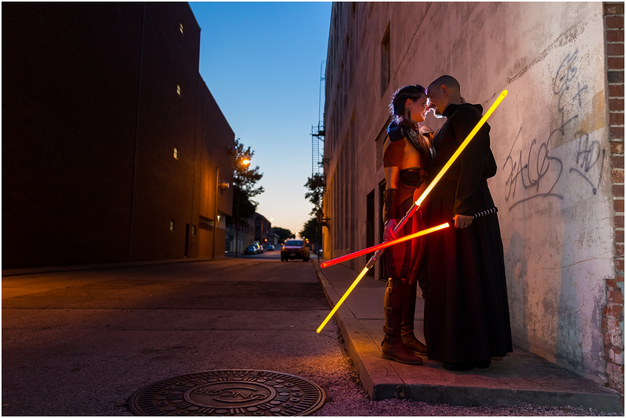 A bride dressed as a Jedi Knight and her groom, dressed as a Sith Lord, embrace holding lightsabers down a darkened alley in downtown Waco, Texas  - Jason & Melaina Photography - www.jasonandmelaina.com