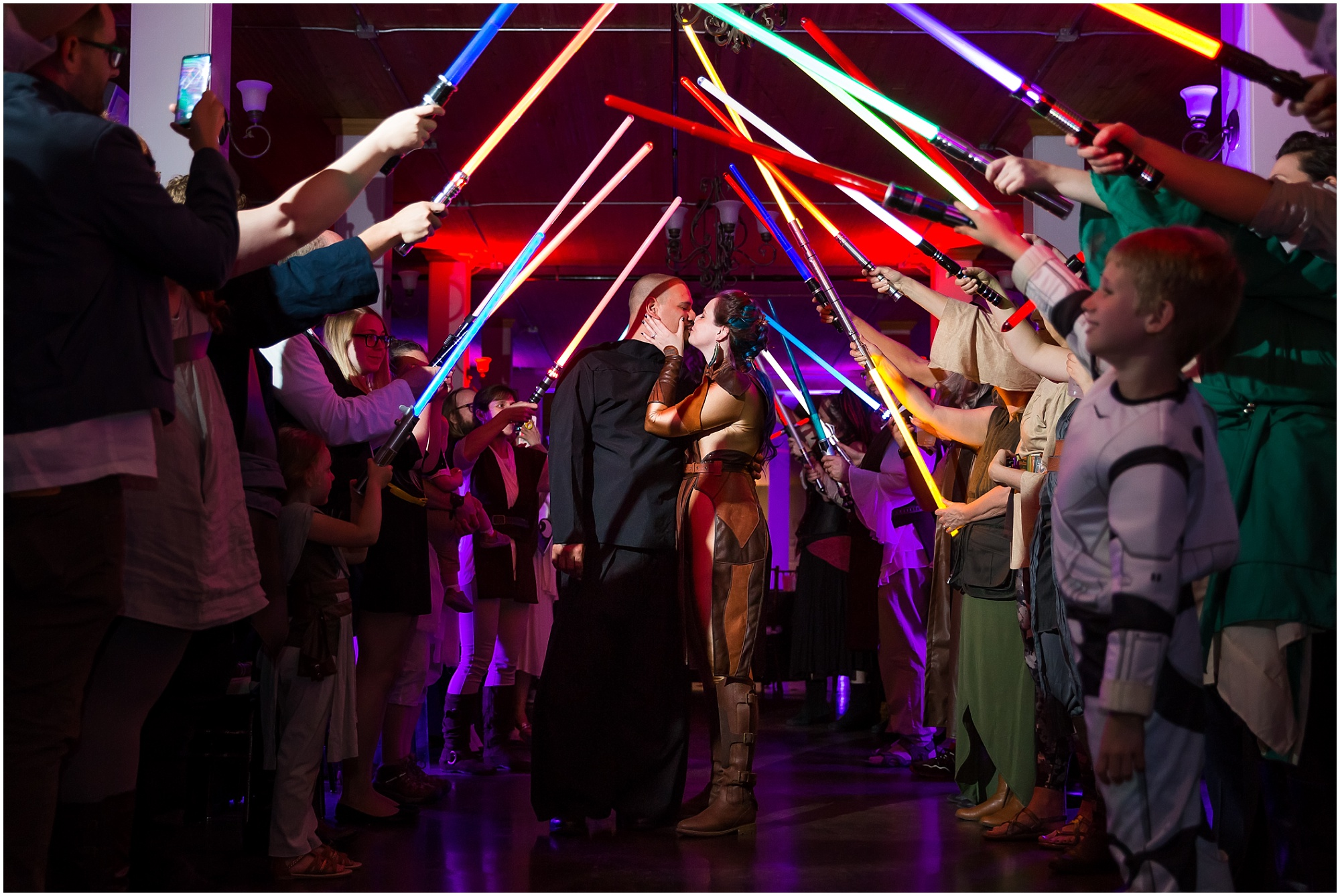 A bride and groom, dressed as Star Wars characters, kiss under a lightsaber tunnel as they leave their May 4th wedding reception - The Palladium at Waco, Texas - Jason & Melaina Photography