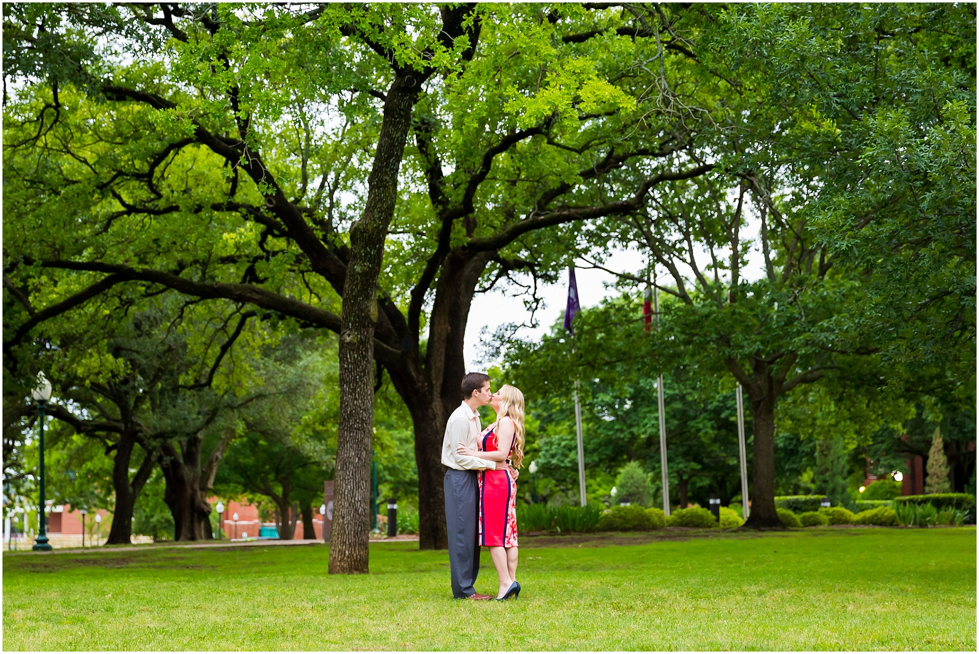 A couple kisses under the large trees in Memorial Park at Tartleton State University, Stephenville, Tx - Jason & Melaina Photography - www.jasonandmelaina.com