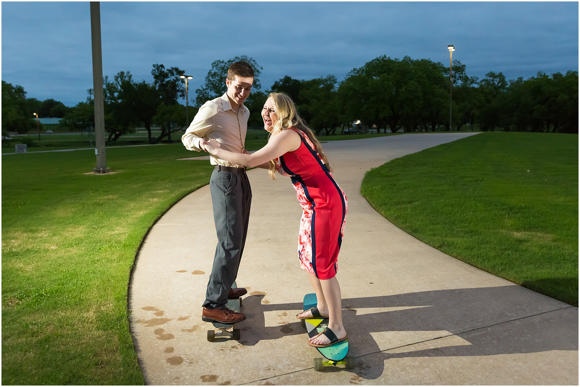 A guy helps his fiance long board down a sidewalk while she laughs during their engagement photos in Stephenville, Texas - Jason & Melaina Photography - www.jasonandmelaina.com