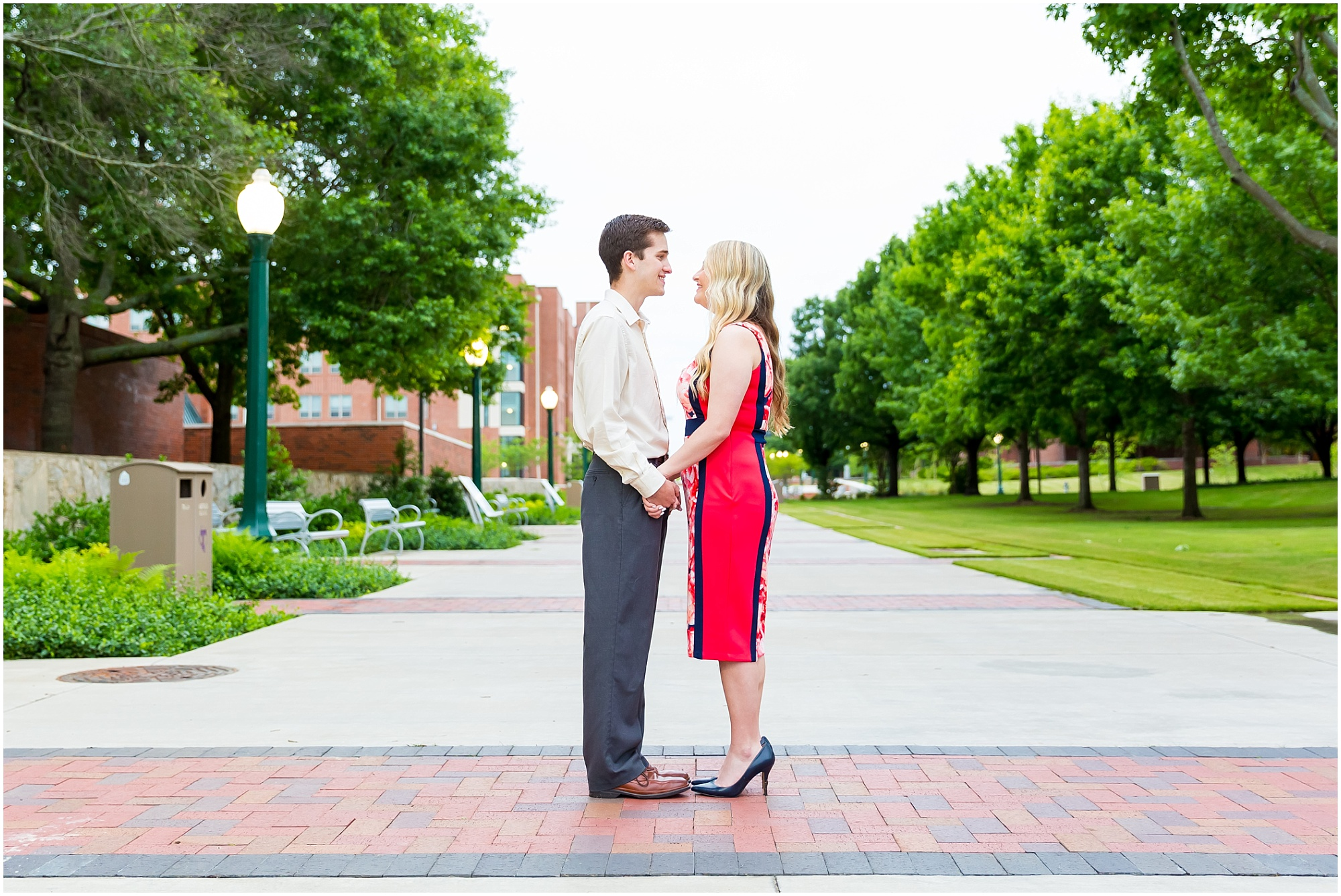 A couple stands in the center of a sidewalk lined with trees and buildings on the Tarleton State University campus in Stephenville, Texas - Jason & Melaina Photography - www.jasonandmelaina.com