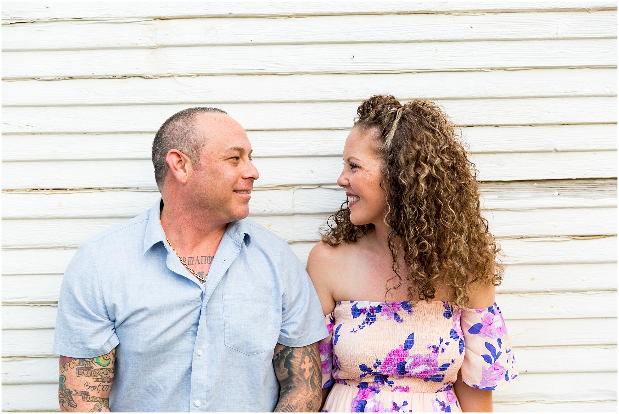 A bride-to-be smiles sits beside her fiance and they turn in towards one another to smile during their engagement session at Glen Rose, Texas - Jason & Melaina Photography - www.jasonandmelaina.com