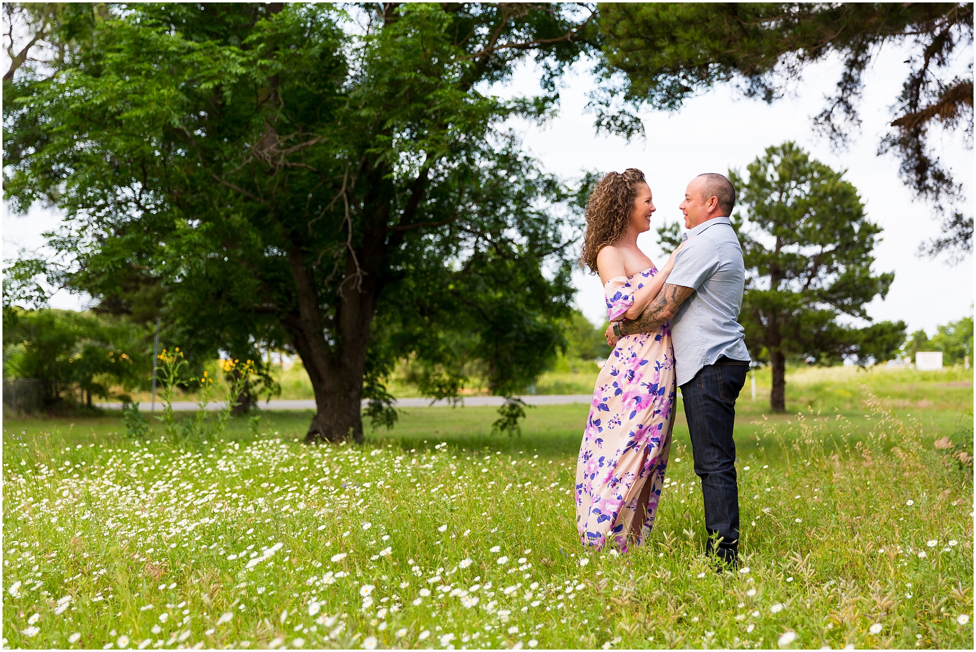 A couple faces one another and holds one another in a field of little white flowers during their engagement session at Glen Rose, Texas - Jason & Melaina Photography - www.jasonandmelaina.com