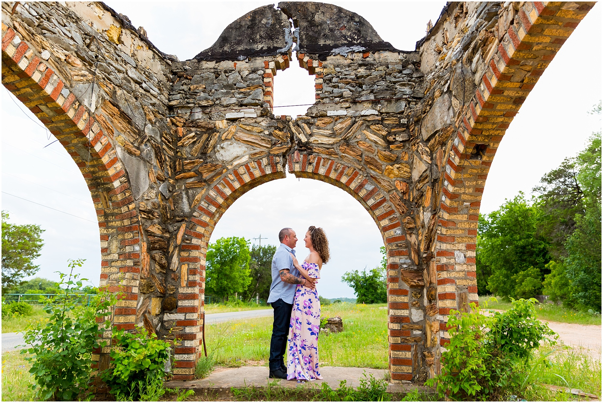 A couple holds one another under an archway of an abandoned petrified rock building in Glen Rose, Texas - Jason & Melaina Photography - www.jasonandmelaina.com