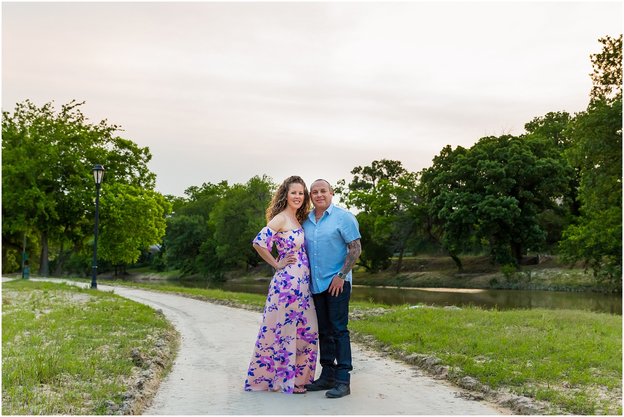 A couple smiles at the camera while standing near a river with a pink sunset sky behind them during their engagement photo session - Jason & Melaina Photography - www.jasonandmelaina.com