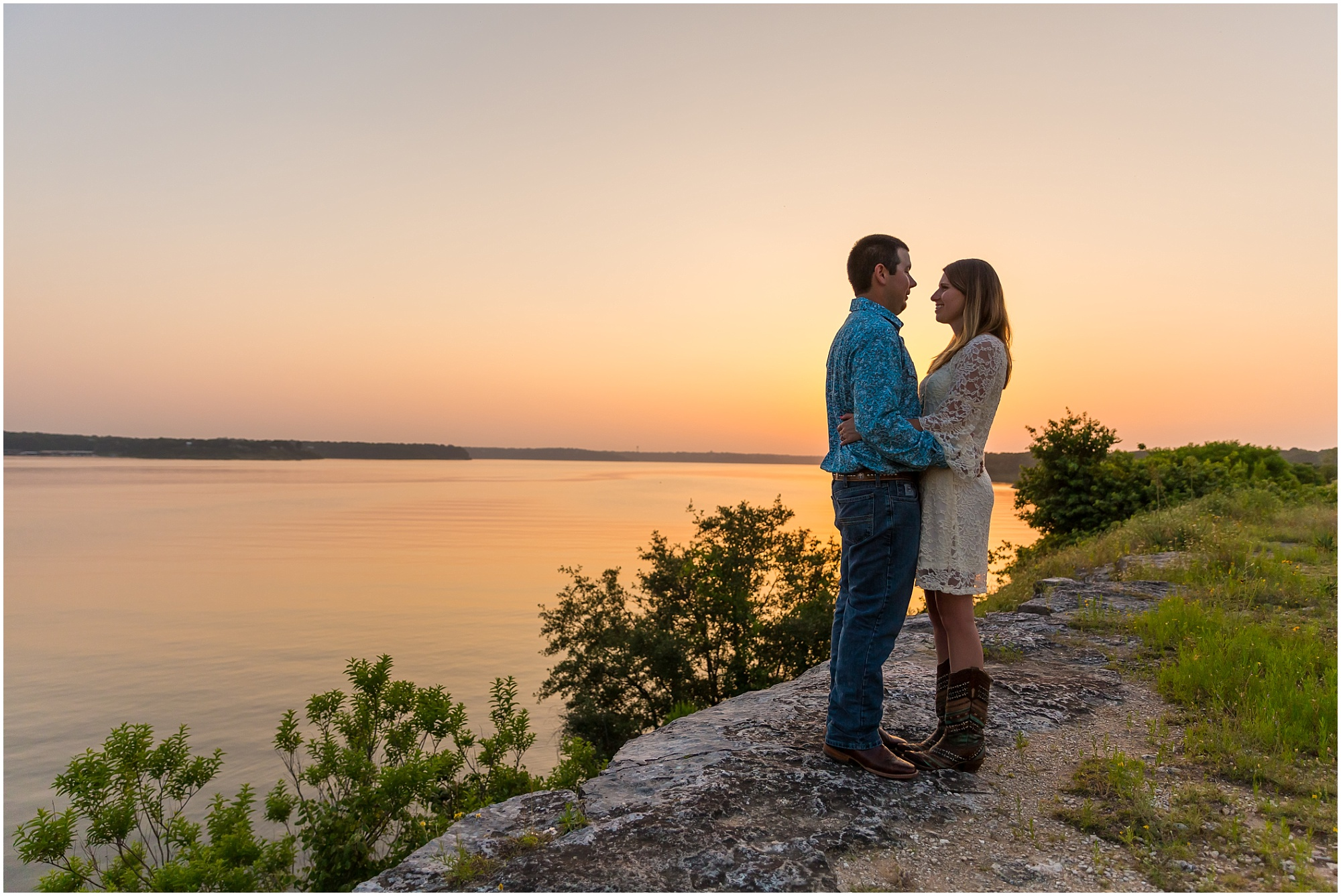 A couple embraces at the Belton Lake Dam while the sun sets over the lake behind them - Jason & Melaina Photography - www.jasonandmelaina.com