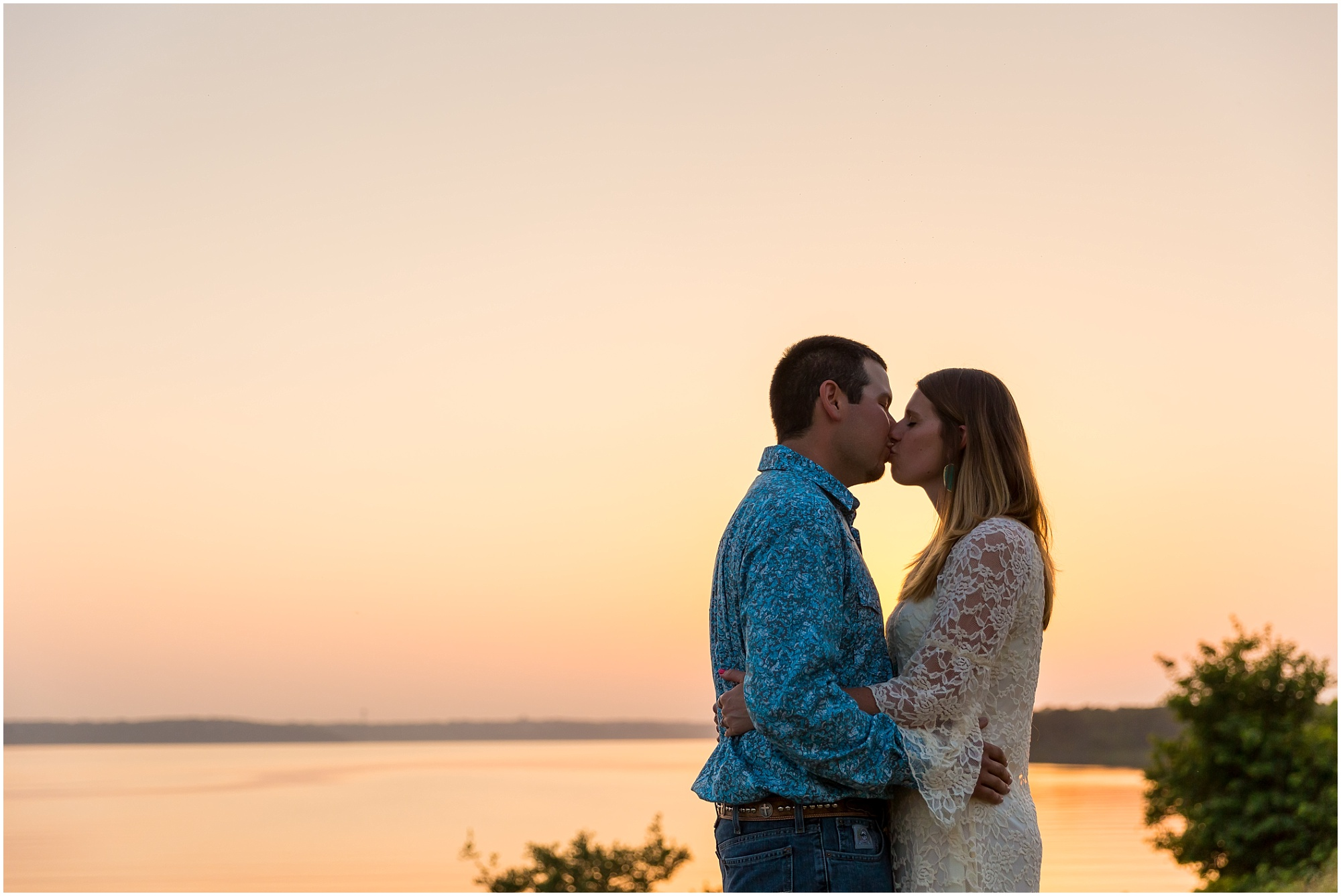 A couple kisses at Belton Lake Dam while the sunset turns the sky orange behind them over the lake - Belton, Texas Engagement session - Jason & Melaina Photography - www.jasonandmelaina.com
