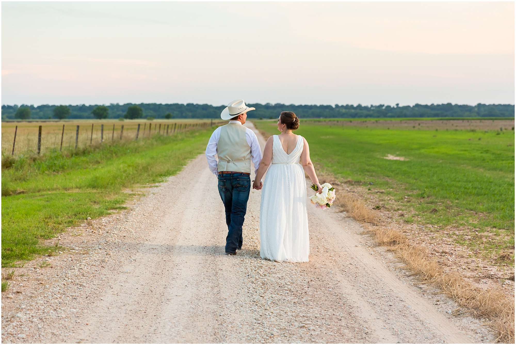 A just married couple walks hand-in-hand down a dirt road outside their wedding reception at Moon River Ranch | Jason & Melaina Photography | www.jasonandmelaina.com
