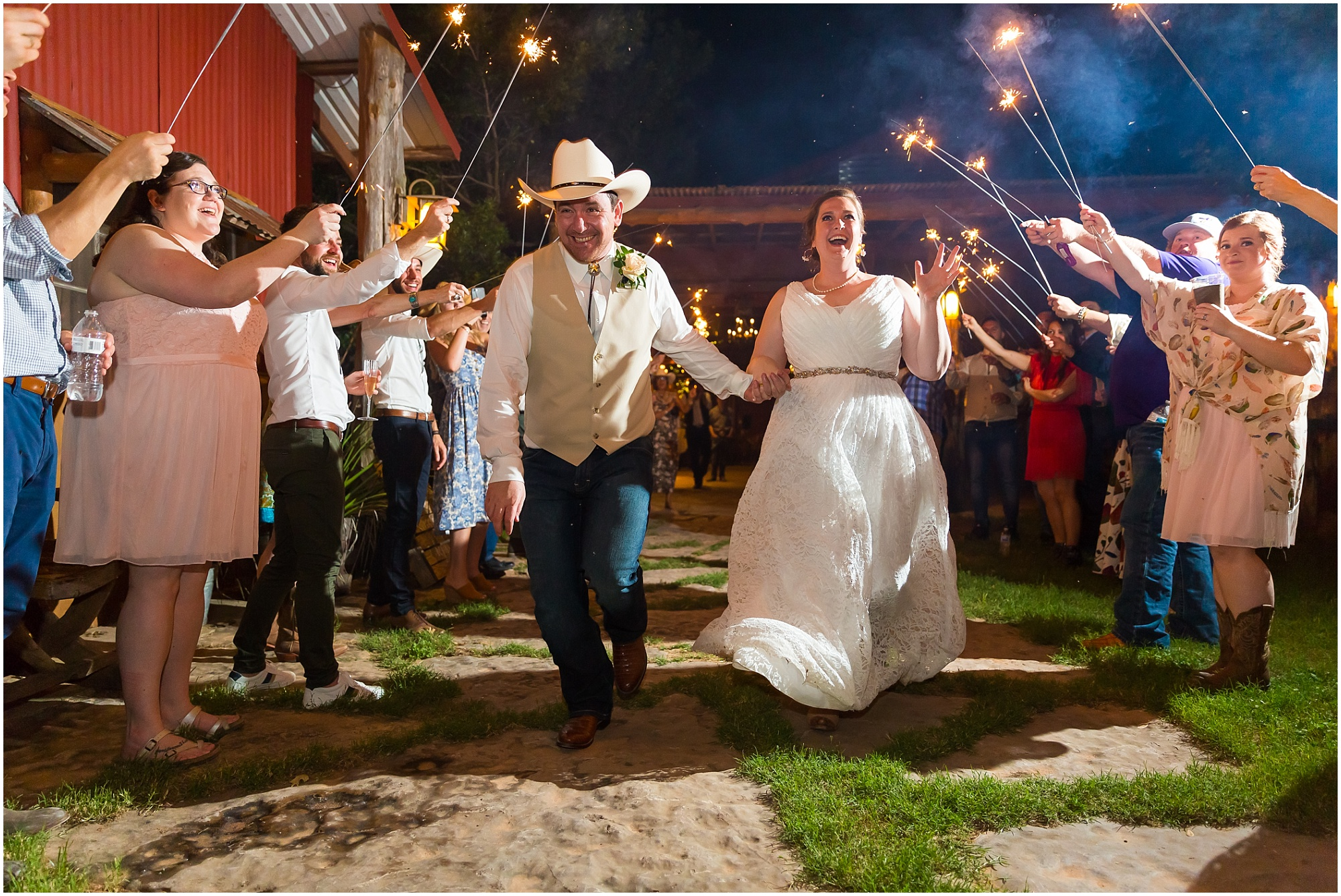 A groom and his bride run through a tunnel of their loved ones holding up sparklers as they leave their wedding reception at Moon River Ranch | Jason & Melaina Photography | www.jasonandmelaina.com