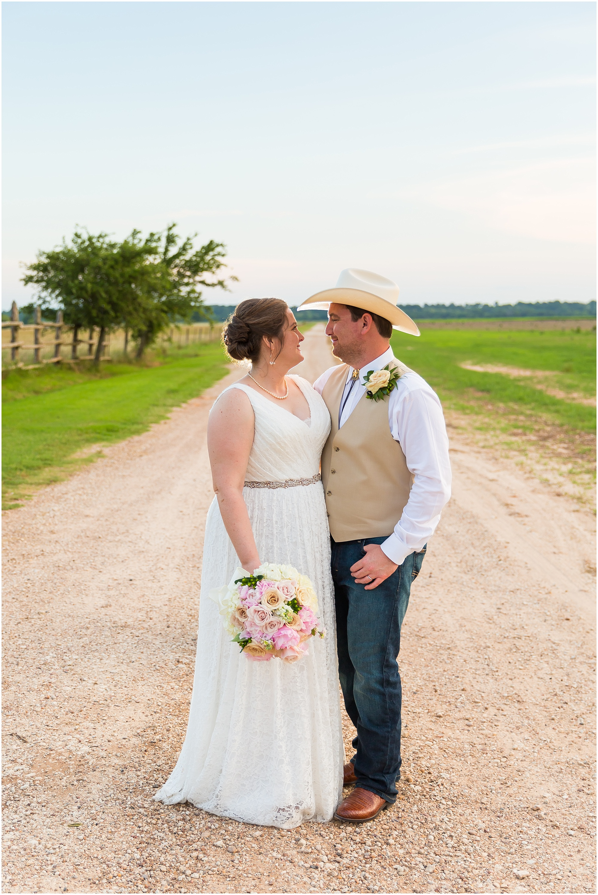 A bride and groom face one another in the center of a dirt road, surrounded by fields at their Moon River Ranch wedding | Jason & Melaina Photography | www.jasonandmelaina.com