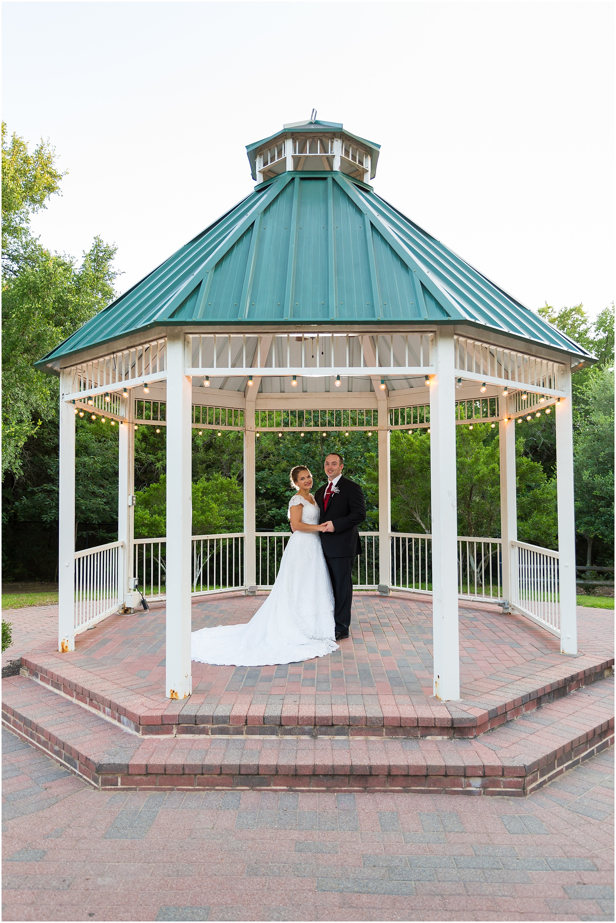 A groom and his bride pose together under the gazebo at Carleen Bright Arboretum in Woodway, Texas - Jason & Melaina Photography - www.jasonandmelaina.com