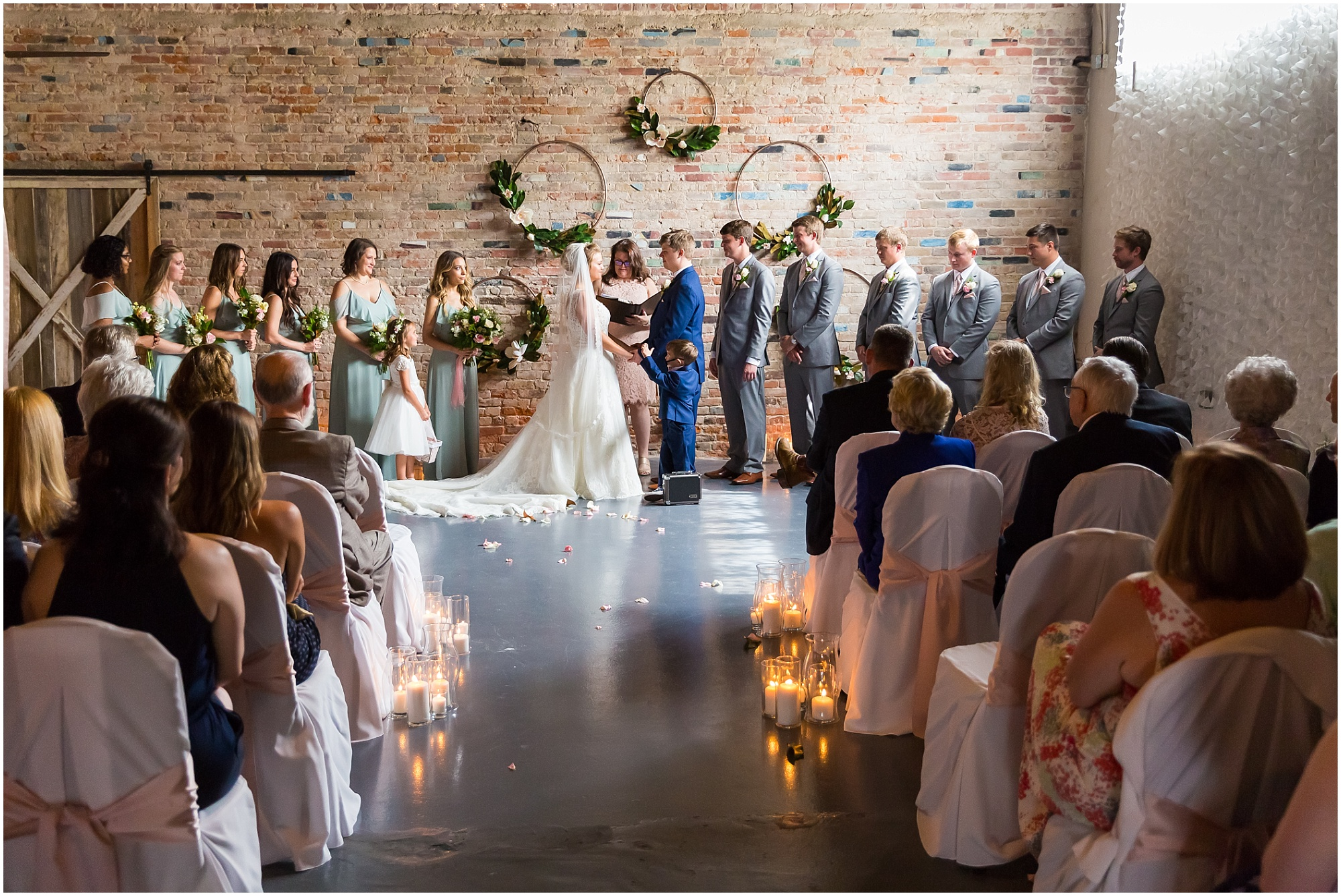 A bride and groom stand together during their wedding ceremony, next to an exposed brick wall with hanging floral hoops at The Eagle Historic Warehouse in Hillsboro, Texas - Jason & Melaina Photography - www.jasonandmelaina.com