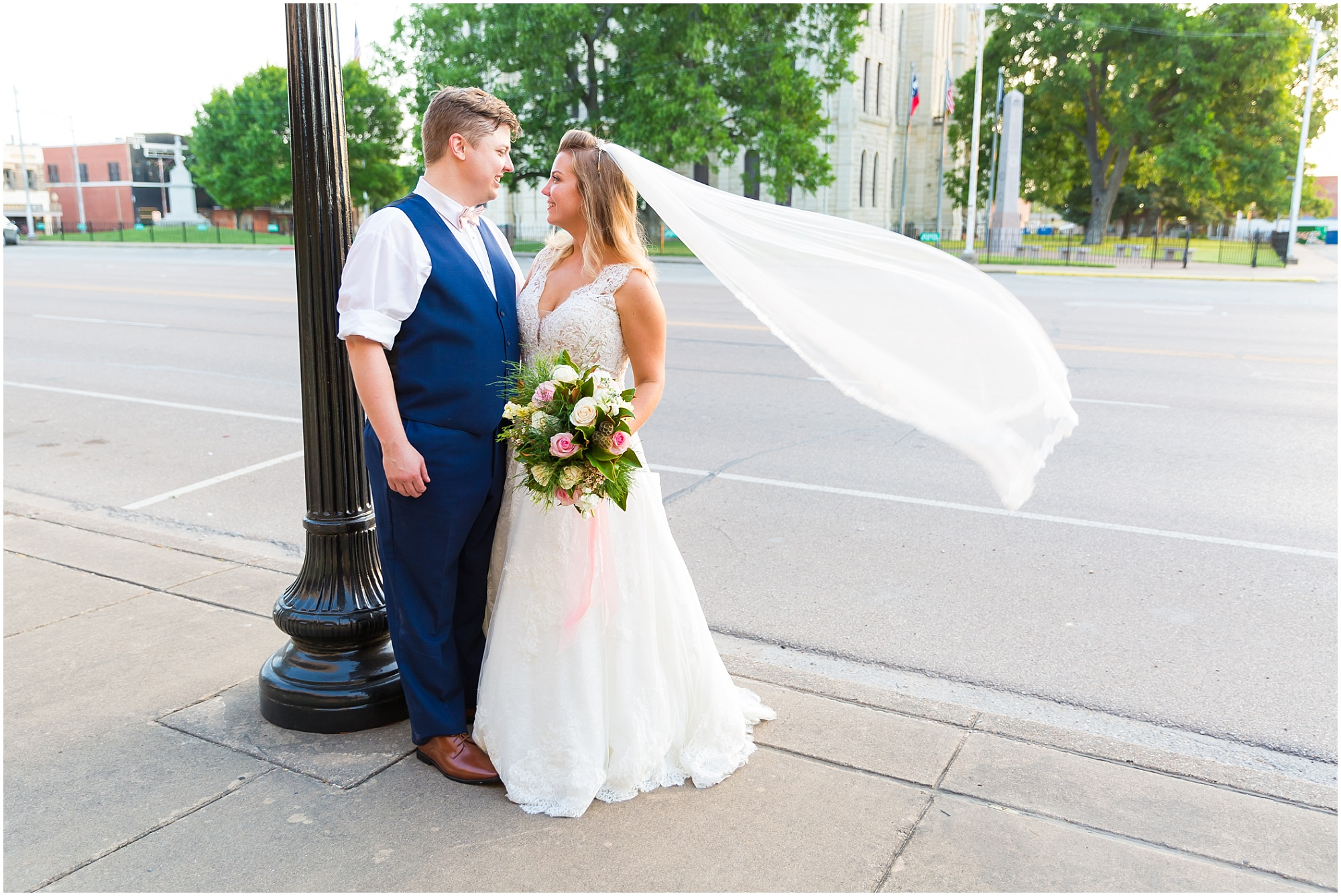 A bride and groom smile at one another as the wind catches the brides veil in downtown Hillsboro, Texas - Jason & Melaina Photography - www.jasonandmelaina.com