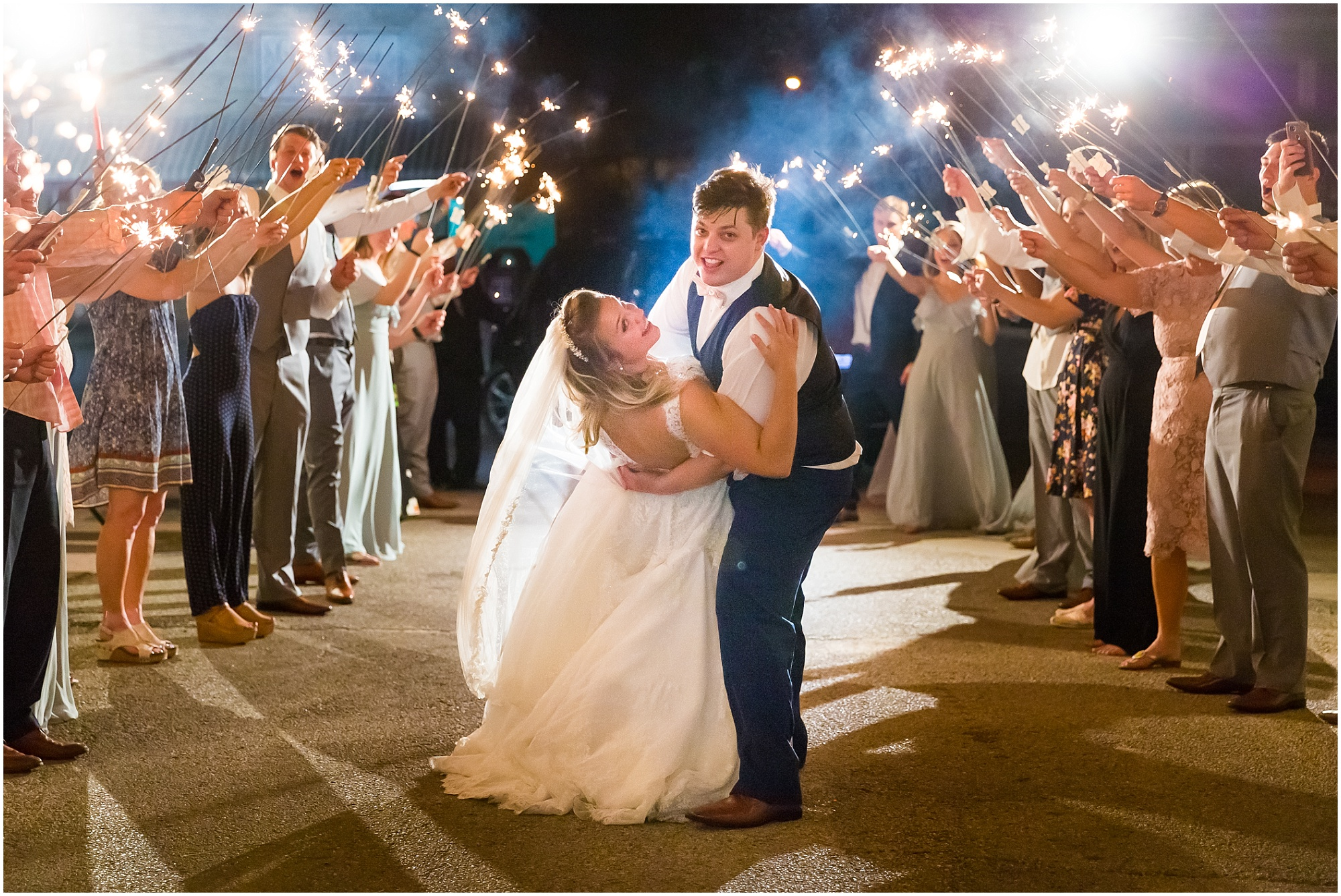 A groom dips his bride as they walk down a tunnel of sparklers as they leave their wedding - Jason & Melaina Photography - www.jasonandmelaina.com