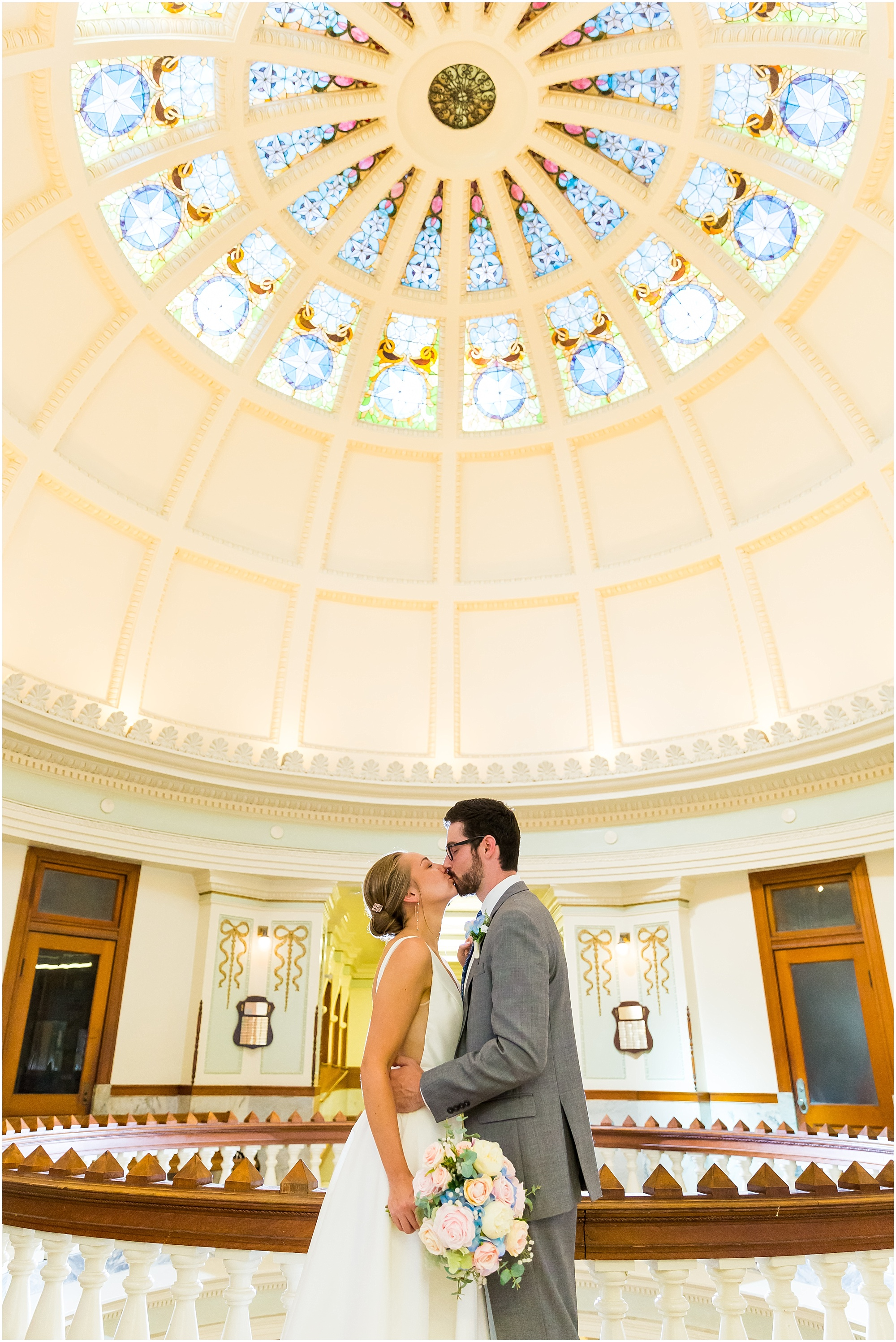 Couple kisses under the stained glass rotunda inside the Waco Courthouse during their courthouse elopement in Waco, Texas | Jason & Melaina Photography
