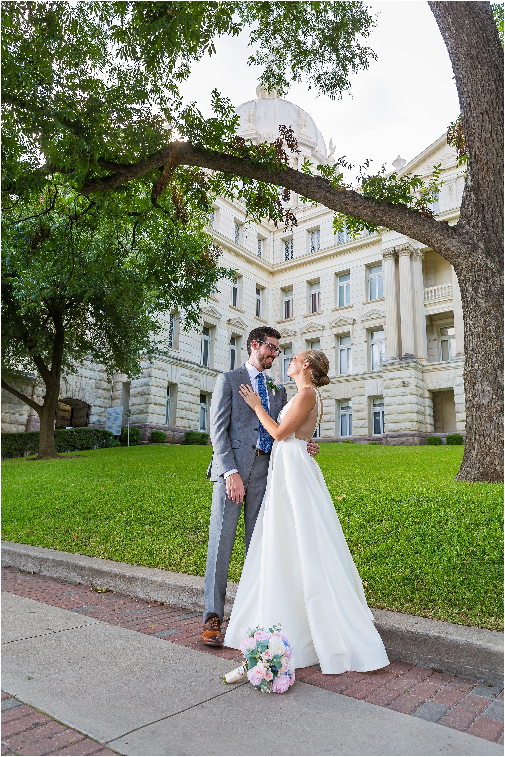 A bride and groom hold one another outside the McLennan County Courthouse in Waco, Texas | Jason & Melaina Photography
