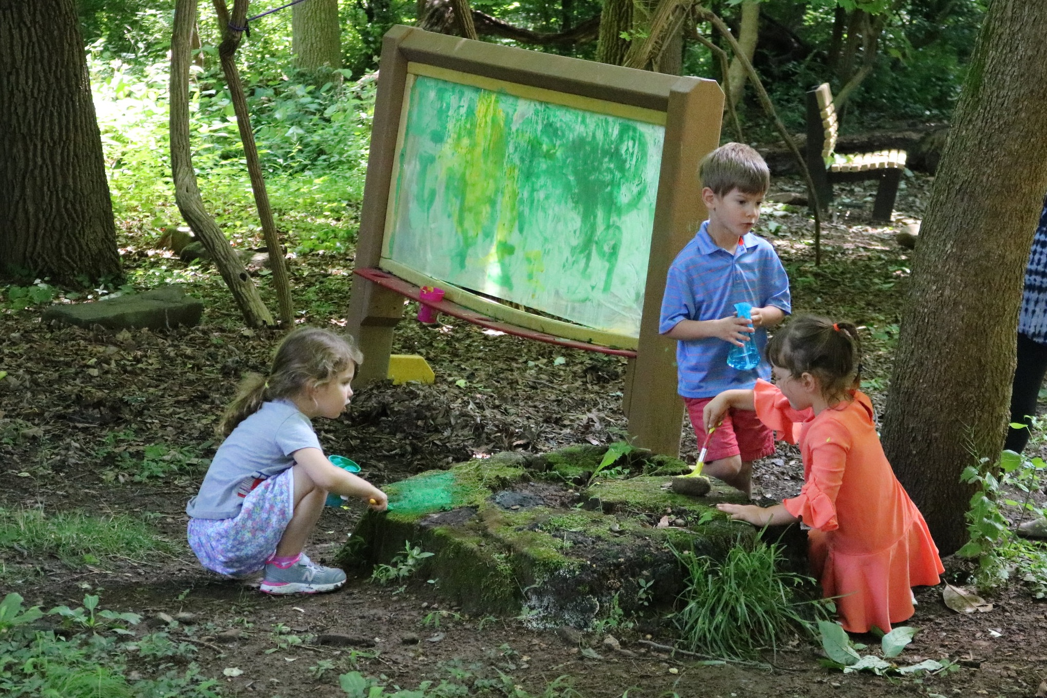 Three preschoolers playing outside, painting rocks in forest