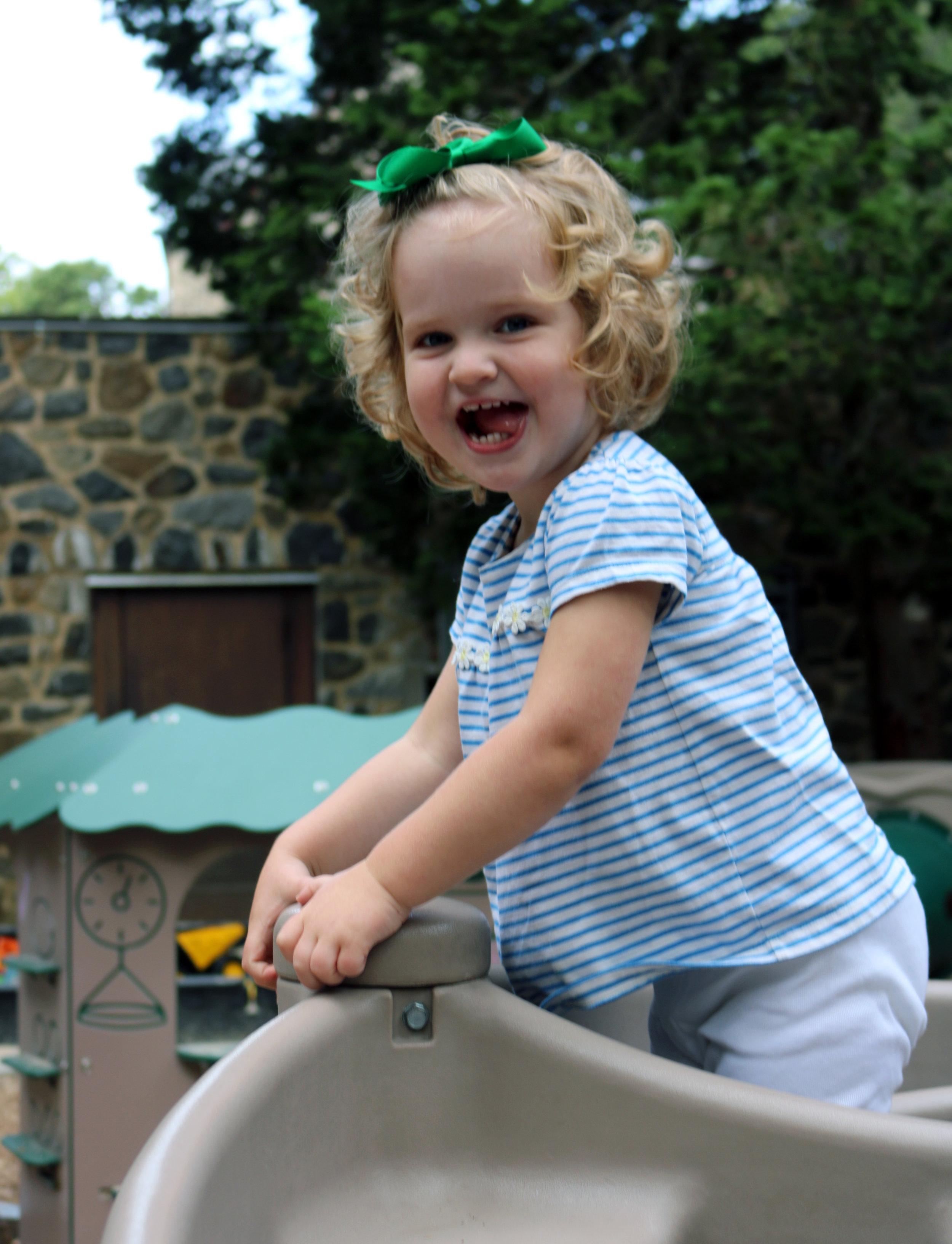 Joyful toddler girl climbing on playground equipment