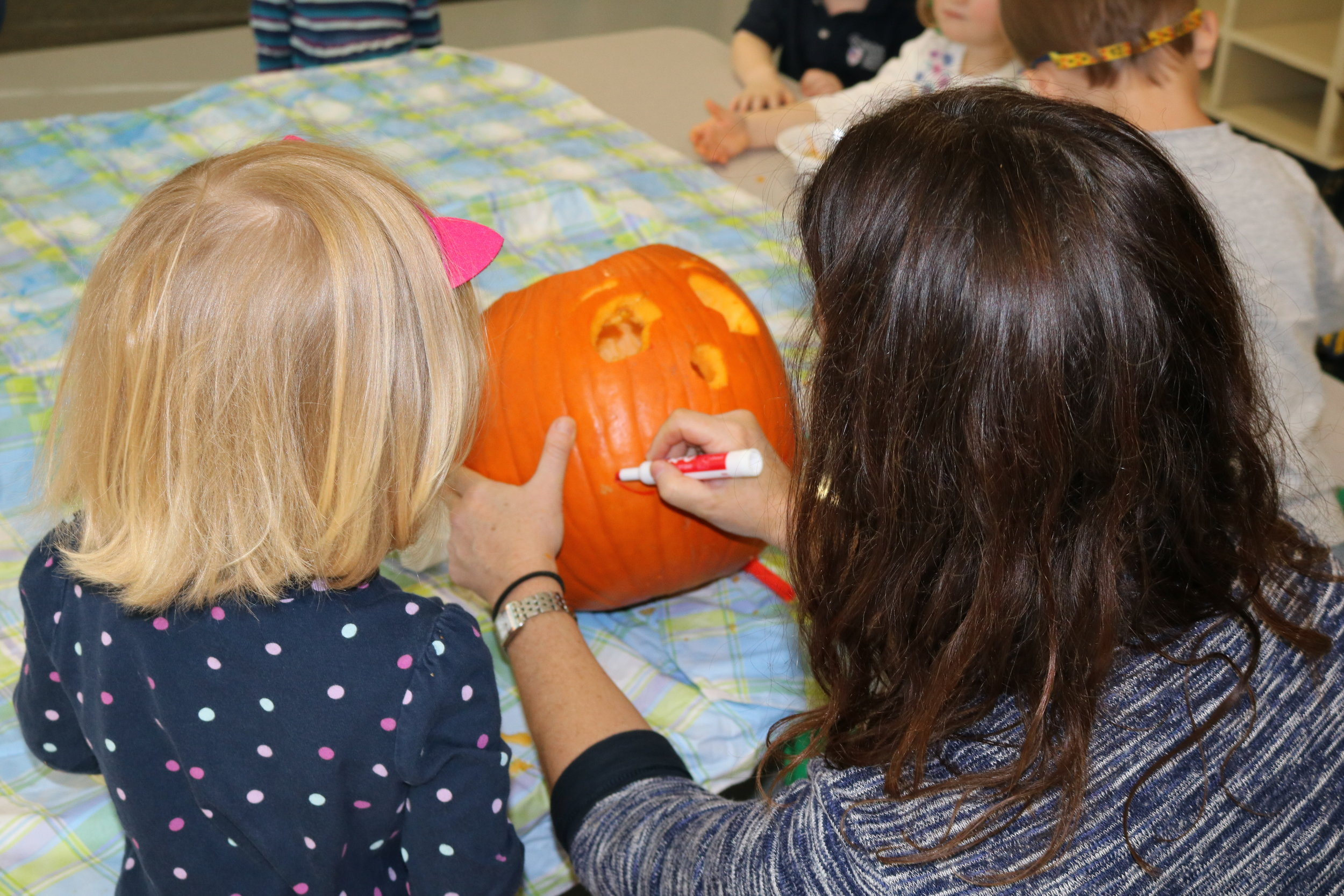 Preschool girl helping teacher make a jack-o-lantern