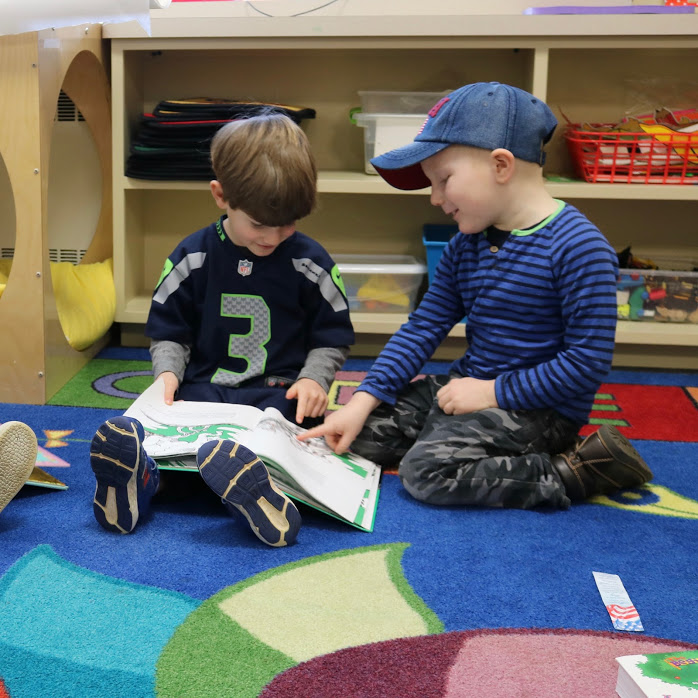 Two preschool boys reading and laughing on classroom rug