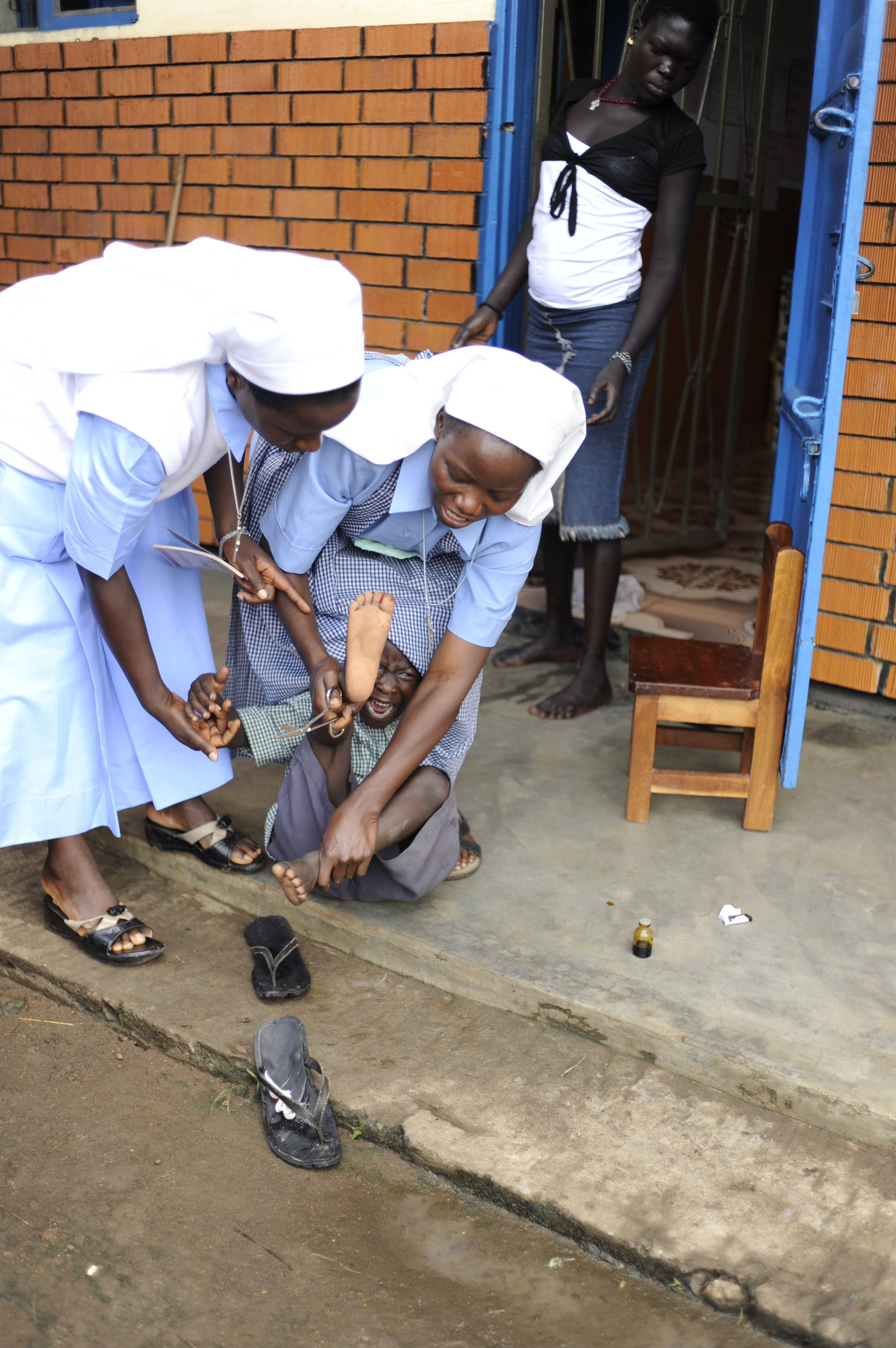 The Evangelizing Sisters of Mary removing a thorn from his walk to school.