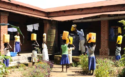Luma students returning from fetching water from Adhu river