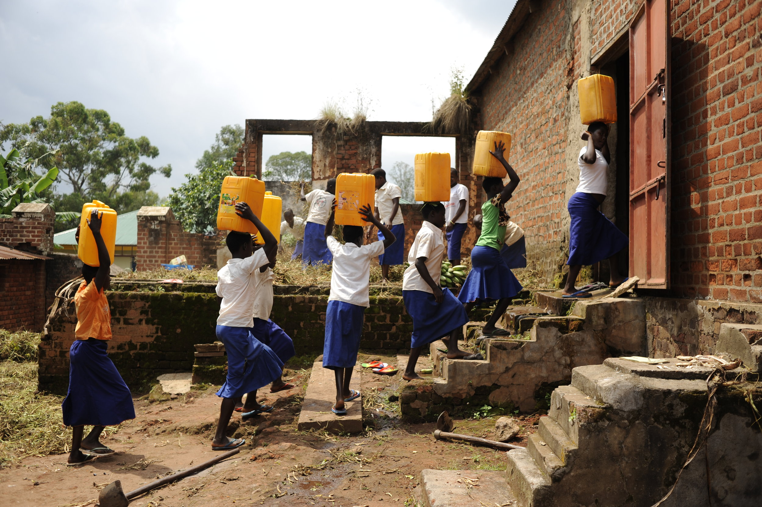 Students fetching water from the river prior to the rain tanks being installed.