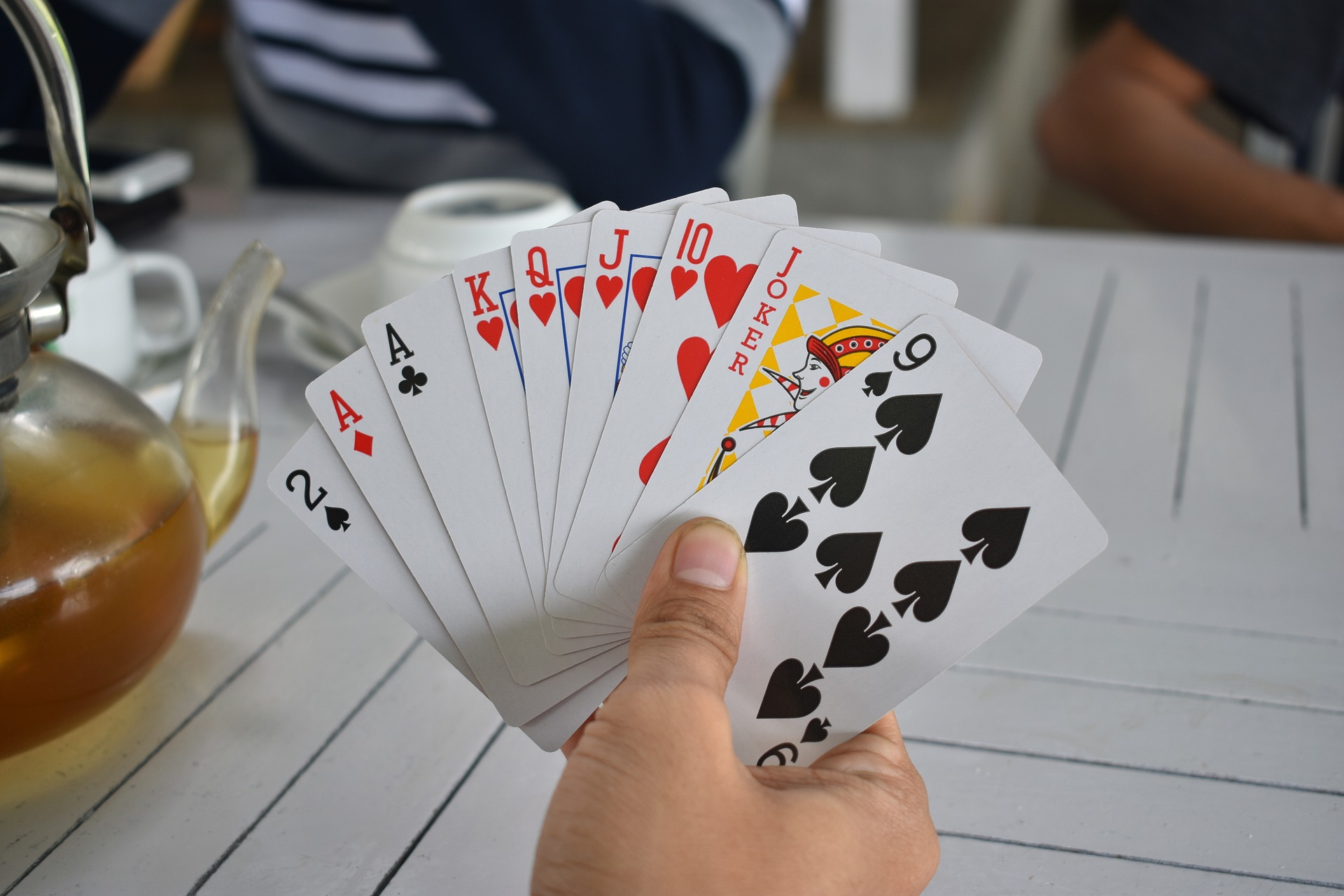 a group of people playing a game of cards.