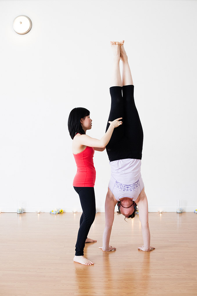 Handstand, adho mukha vrksasana. Place hands shoulder-width apart. Keep the chest open with arms and shoulders strongly engaged. Draw the navel towards the spine. Internally rotate thighs.