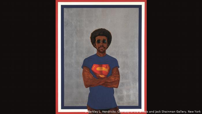 """""""The title image of the """"Soul of a Nation"""" exhibition at London's Tate Modern is a bold, life-size portrait. Barkley Hendricks has painted himself into the picture, naked from the waist down, calm and almost nonchalant. His Superman t-shirt recalls a quote made by Black Panther founder Bobby Seale, who once declared in court: """"We're hip to the fact that Superman never saved no black people."""""""
