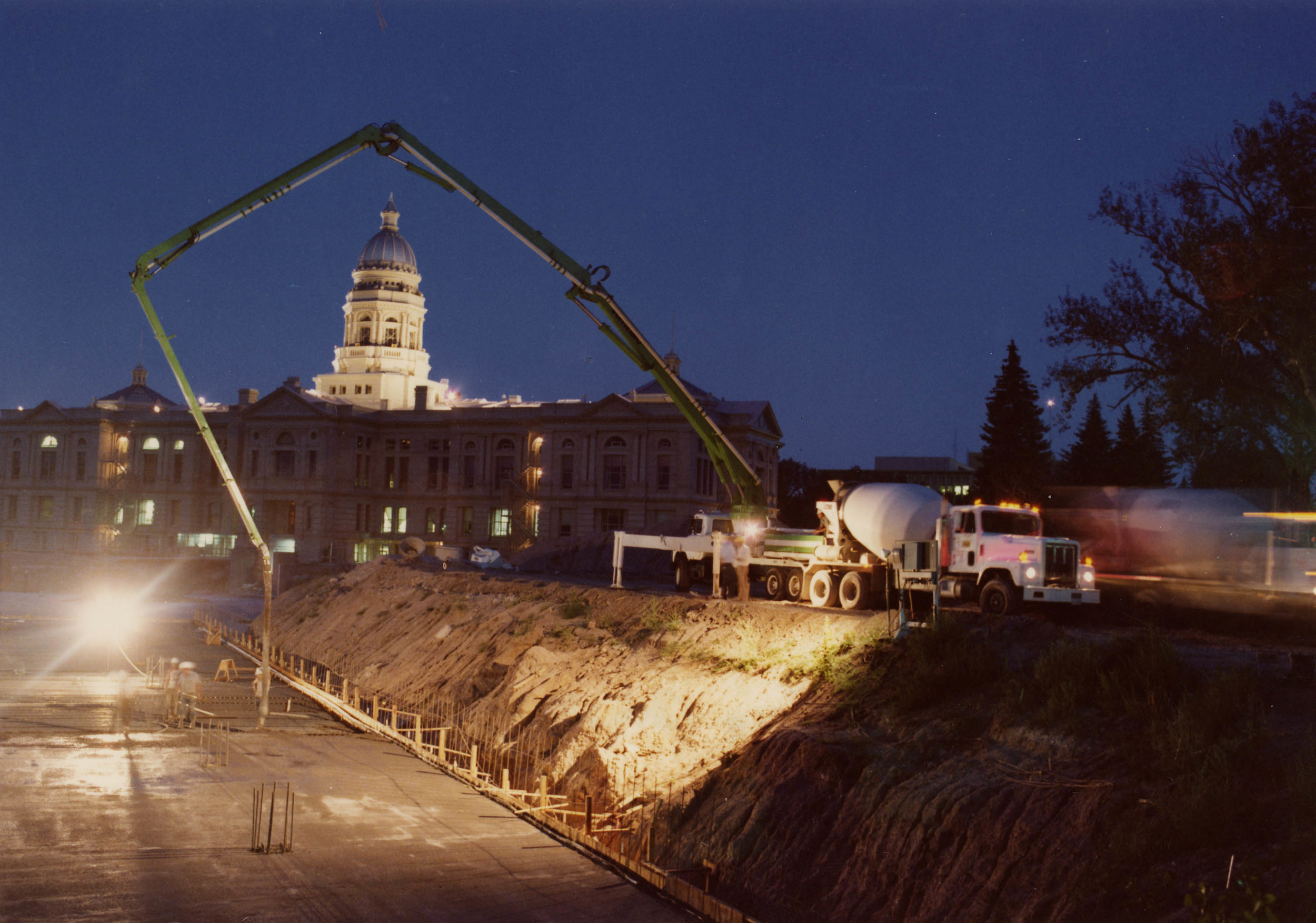 Pouring concrete foundation with pumper truck, Capitol in background at night, 5-1981