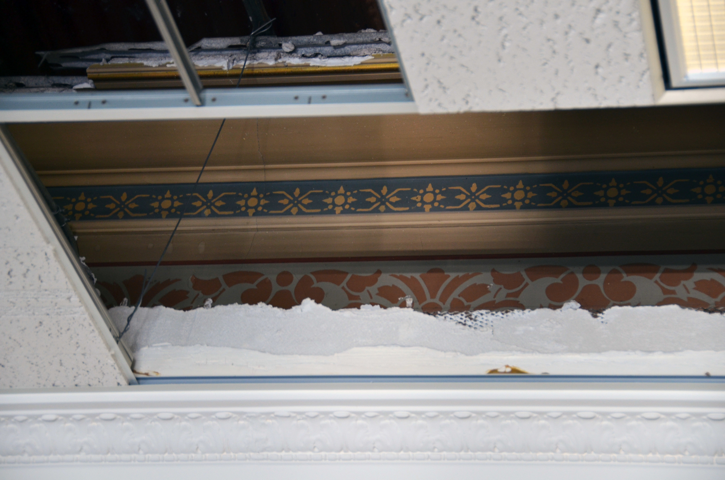 As ceiling tiles are removed in the former Secretary of State's Office, historic paint patterns and crown molding appear.