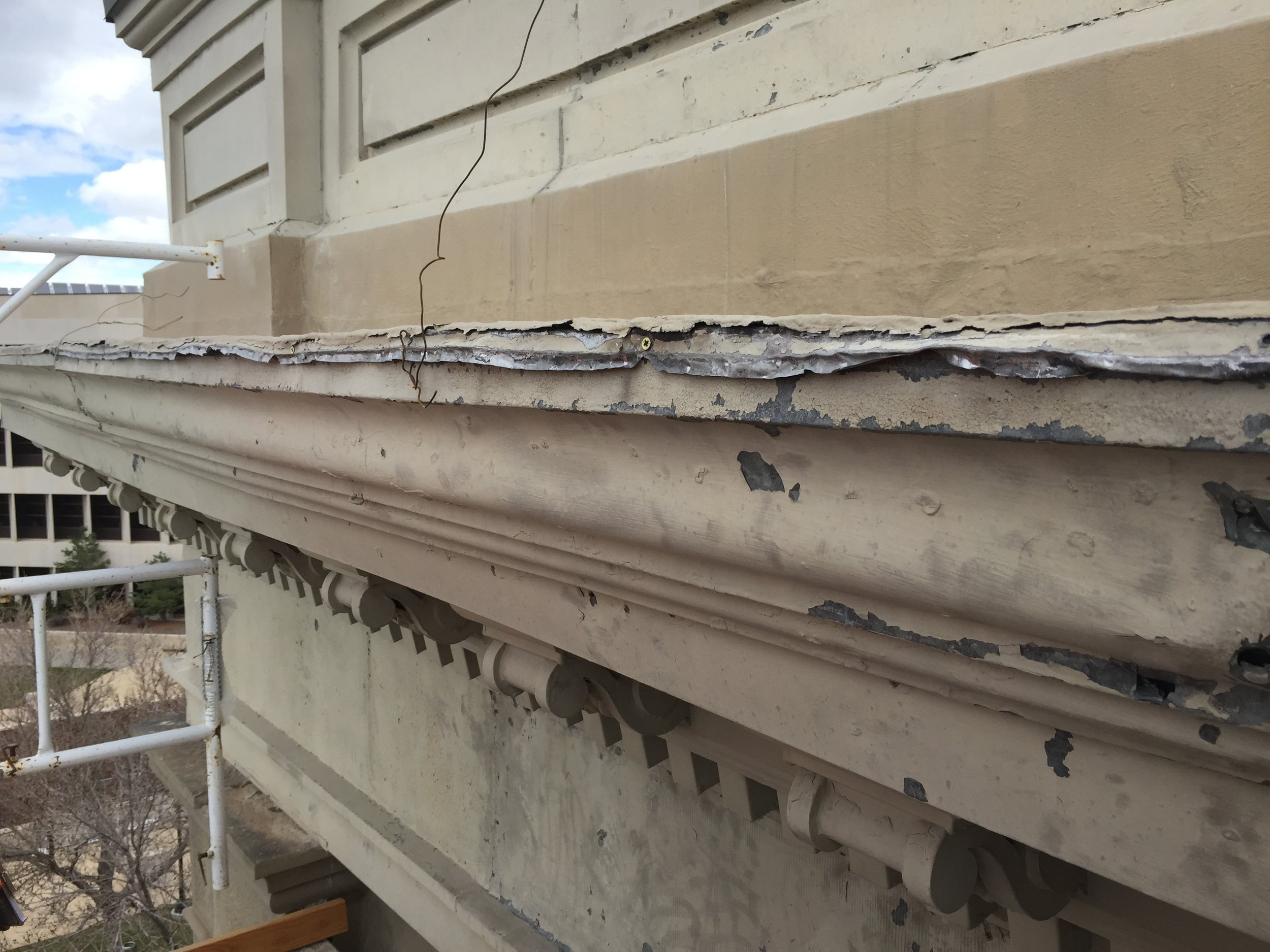 The damaged external entablature, made of sheet metal, is being replaced and a structurally sound steel system will secure it to the building.