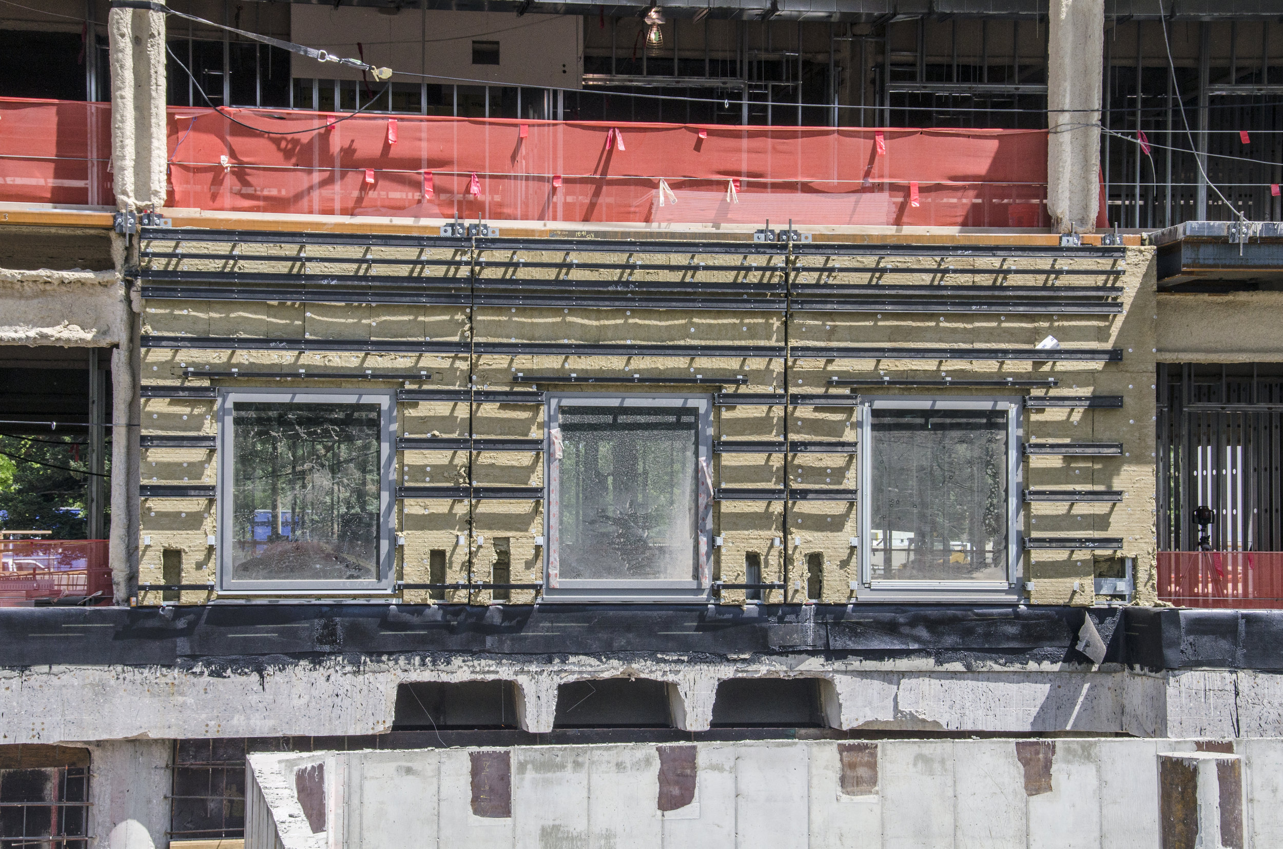 When first placed on the building, the wall panels will look unfinished with just the windows, stone support system and the tan-colored insulation in place. The stone will be installed after the wall panels are secured to the building.