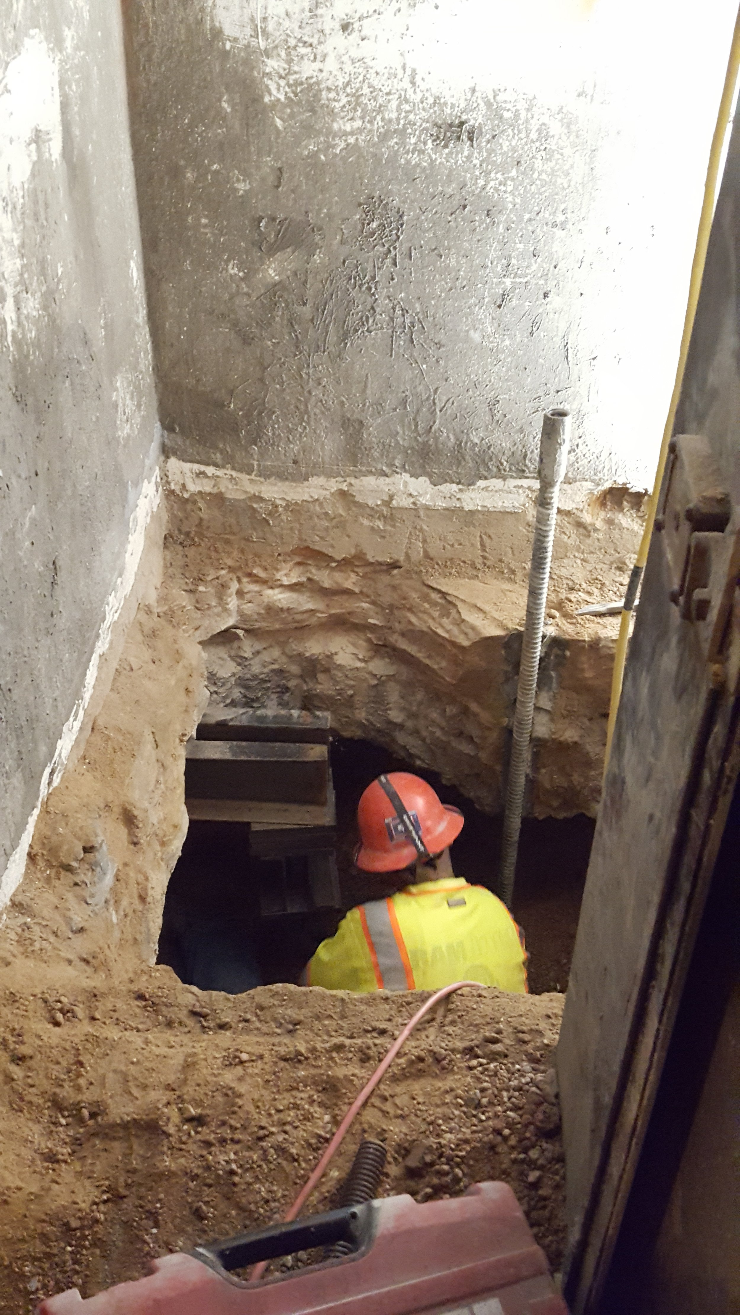 - A worker digs out the footing around an inserted needle beam.