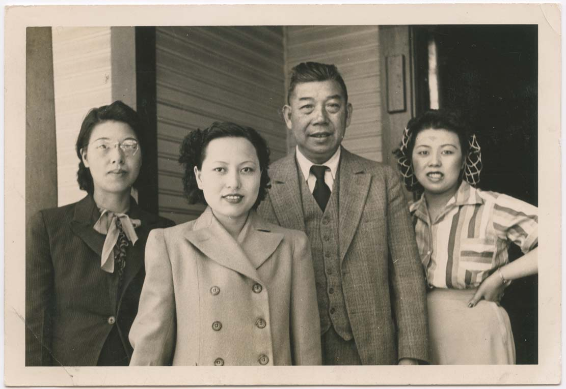 """IRENE LUM (CENTRE LEFT) WITH HER """"PAPER FAMILY,"""" THE WONGS. PHOTOGRAPHED BY JIM WING YUEN. 1940-1941. VICTORIA, BRITISH COLUMBIA. GELATIN SILVER PRINT. GIFT OF THE LUM FAMILY. COURTESY OF THE FAMILY CAMERA NETWORK AND THE ROYAL ONTARIO MUSEUM."""