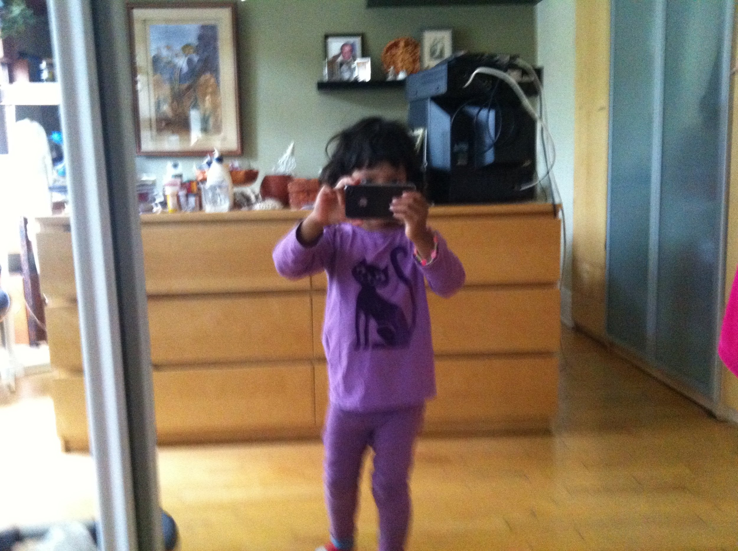 Leena with an iPhone 4. Photographed by Leena. Around 2011. Toronto, Ontario. Digital photograph. Gift of the Sinha/Brendemühl family. Courtesy of The family Camera Network and the ROM.