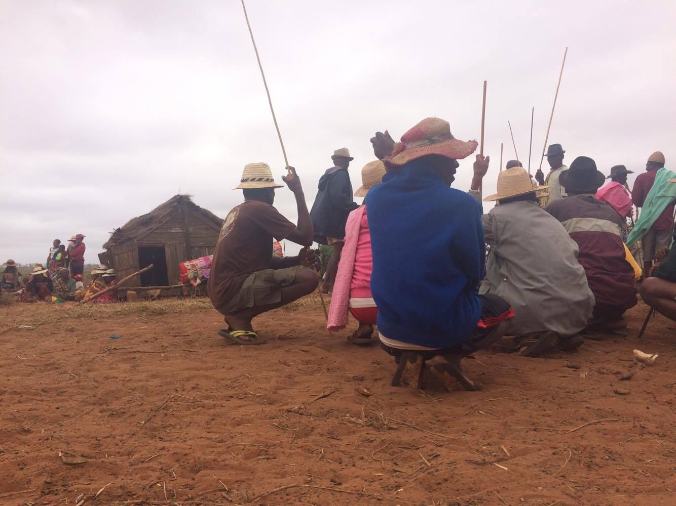 Older male attendees huddled together, holding long sticks or spears.