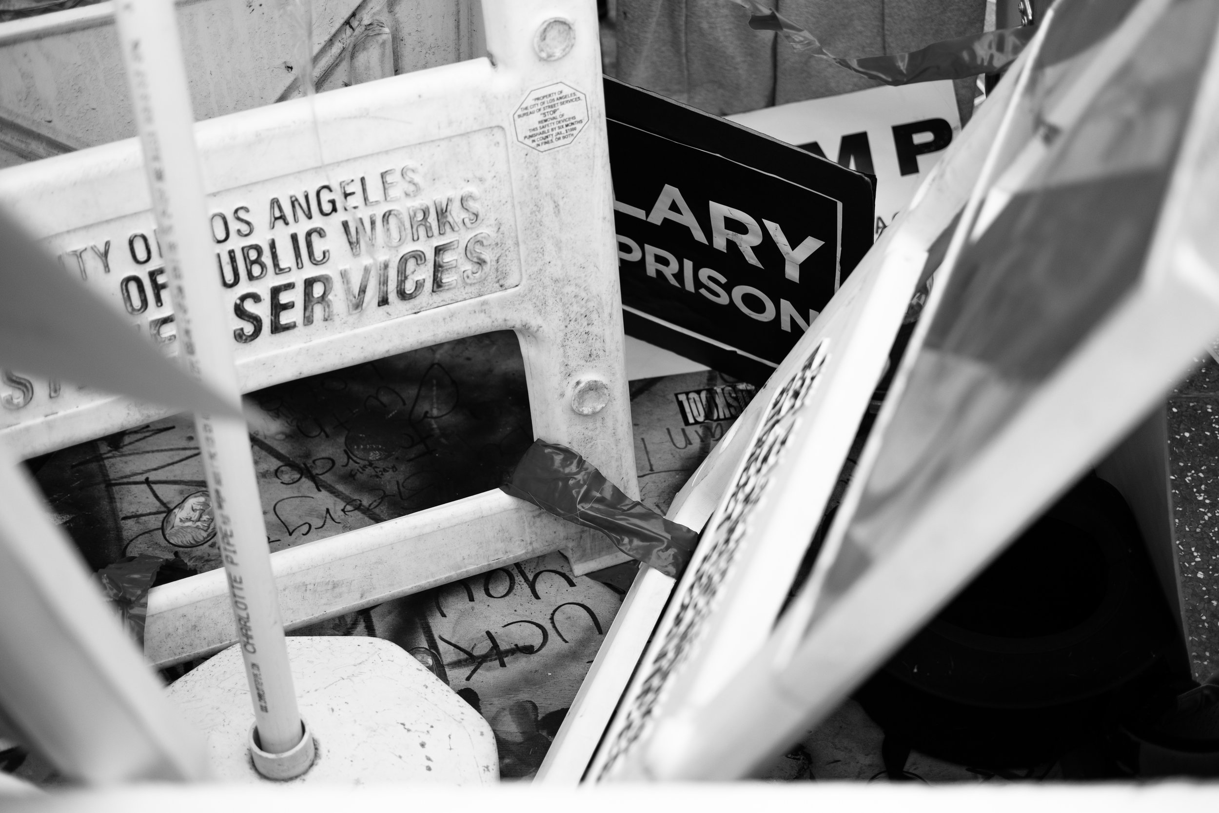 Under the signs and covered by cardboard lay the remains of the vandalized star on the Hollywood Walk of Fame belonging to now President Elect Donald J. Trump.