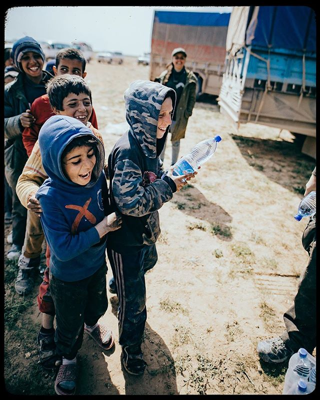 A single sunbeam is enough to drive away many shadows - St Francis of Assisi  Resilience describes the Syrian children. They have seen the darkest things our world has to offer, however still manage to embrace joy in the simplest of things.  Image: Dave Eubank starts a game, tossing bottles to children as they line up for food and water.  #fbr #syria #baghuz #bagouz #framez #doc #docfilm #documentary #canon5dmarkiv #humanitarian #missions #reliefwork #freeburmarangers #displaced
