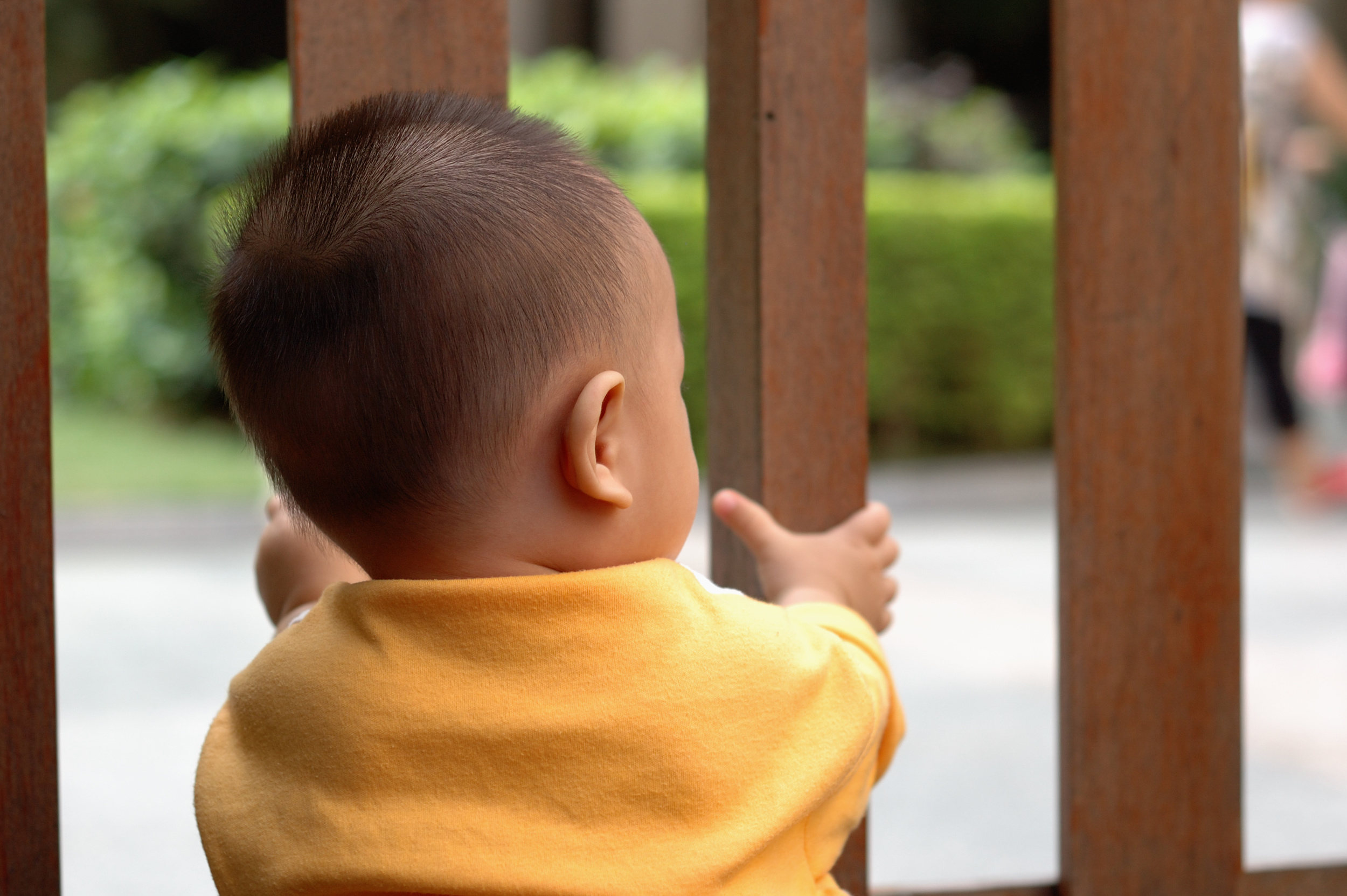 Child standing at baby safety gate and how to pick the right baby gate for your home.