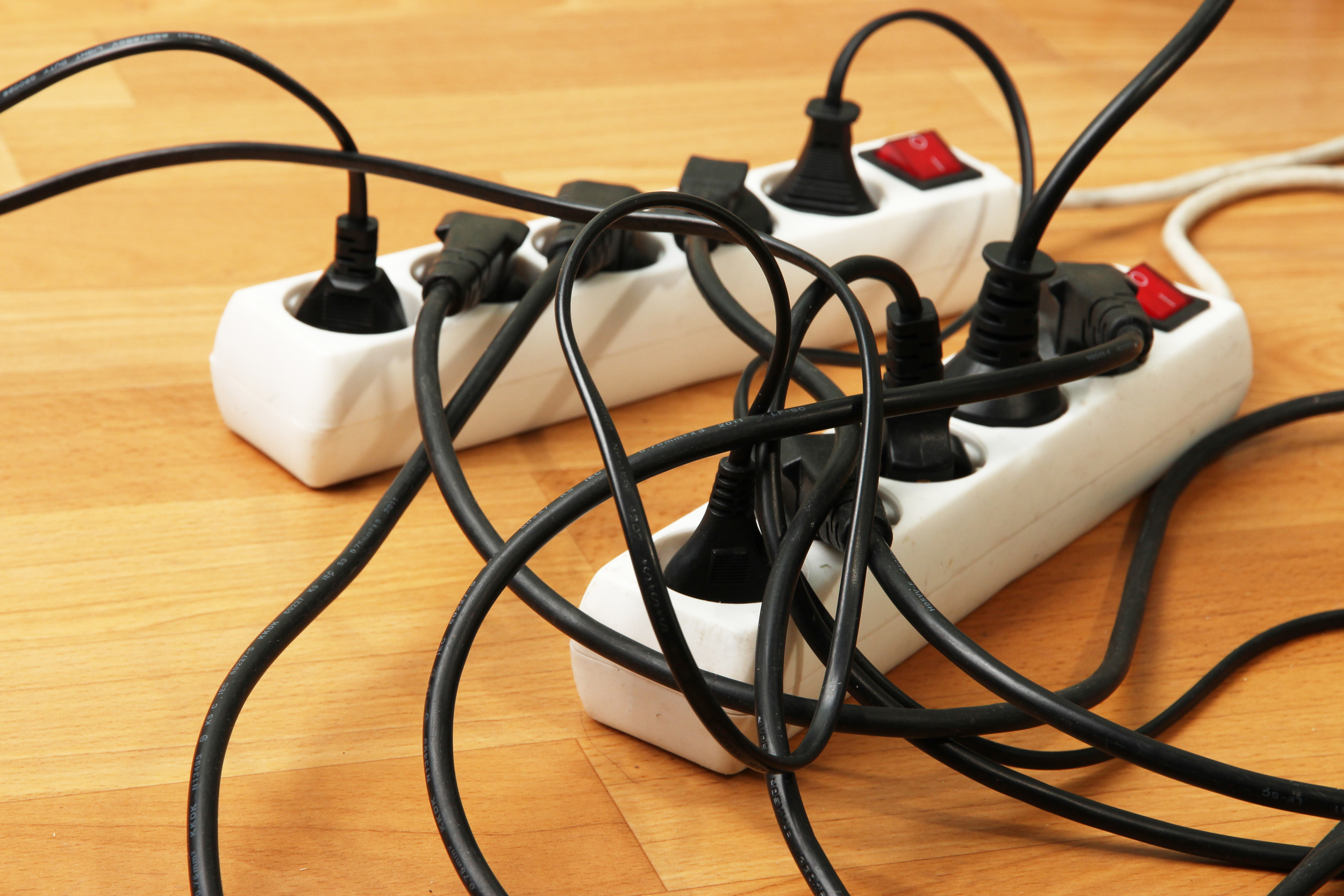 Tame power strip cords with a strip protector.