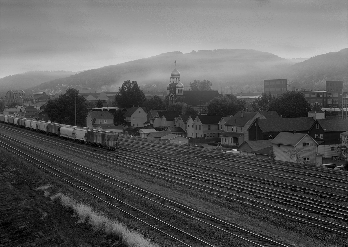 The sleepy Borough of Franklin wakes up in a low fog alongside former Woodvale Yard on the PRR mainline about 275 miles West of Philadelphia's Broad Street Station. Like many local communities Franklin has a prominent church, St john the Baptist that stands dominant along the nearby mountain ridge.