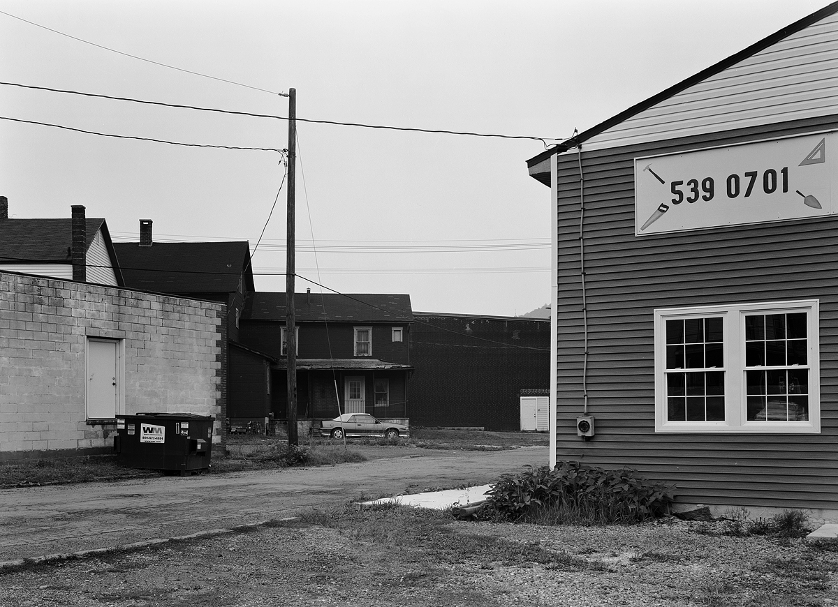 Small businesses flank quiet side streets that run parallel to the former PRR Mainline and Woodvale Terminal. This is a view from Davis Street between Cherry and East Railroad St.