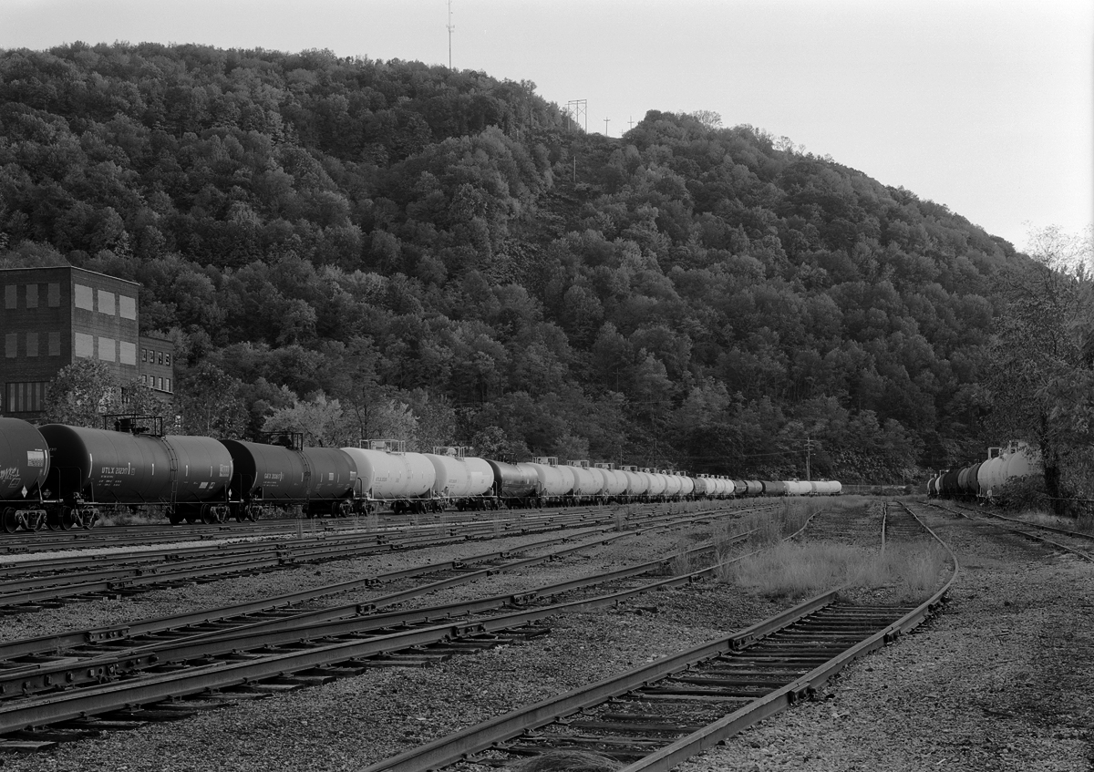 Stored tank cars awaiting reconditioning. The weedy yard and empty tracks of the C&BL interchange yard speak of the impending shut down of Railcar America facility which happened in 2008.