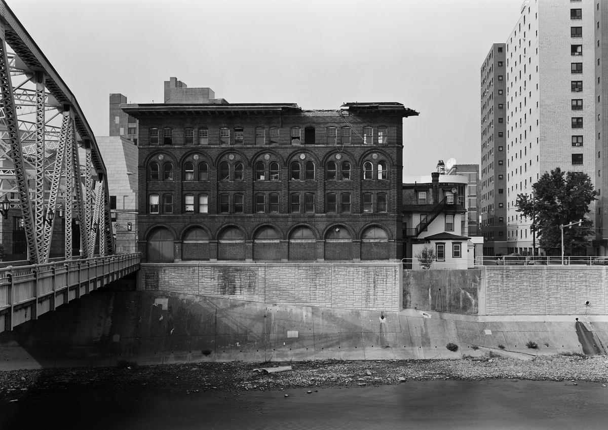 View looking Northeast of Franklin Street Bridge across the Stoneycreek River from Somerset Street. Building on the far side is the Conrad Building which dates from 1900  .