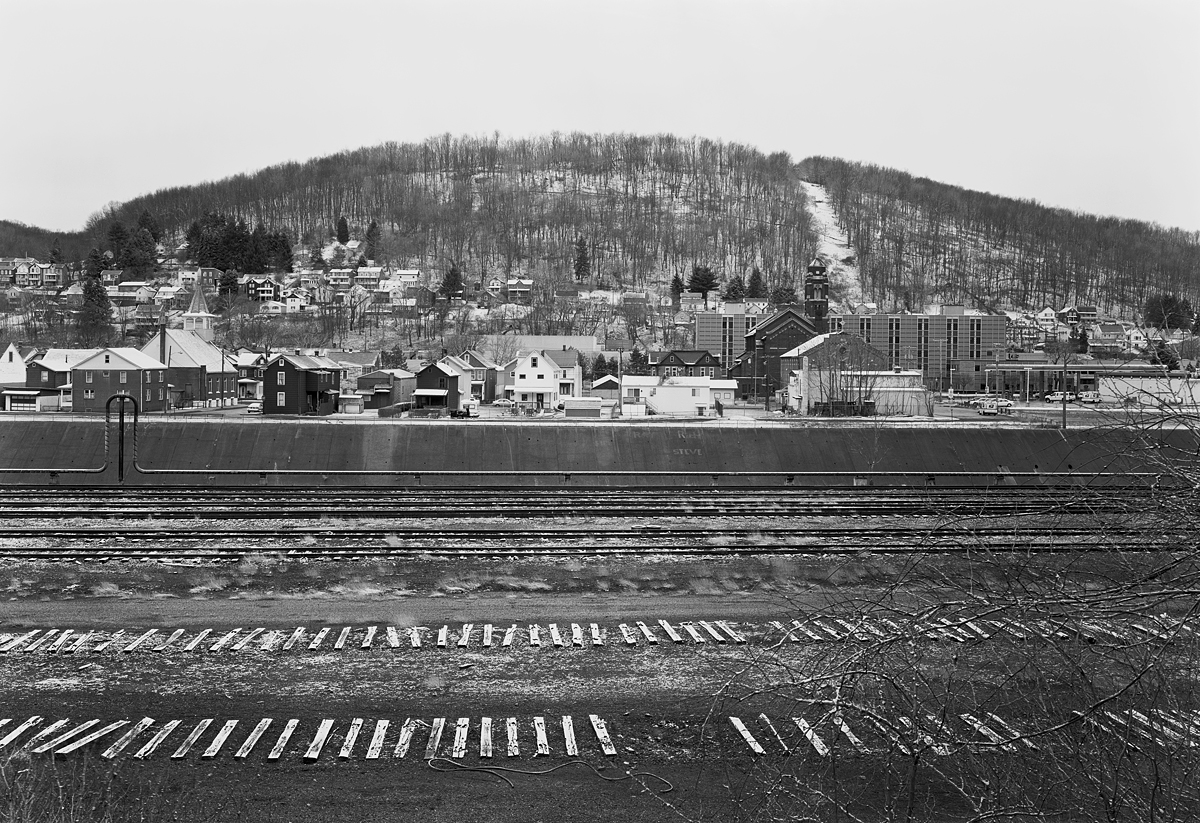 View of Brownstone Hill from the former Conemaugh and Black Lick rail yard on the North Side of the Conemaugh River. The mainline threads along the base of the mountain in the back lots of commercial and industrial buildings along Route 56 from left to right in the photo.