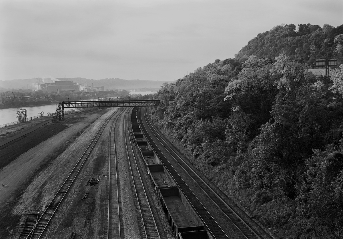 View southeast from the Rankin Bridge of the Mon Line and Union Railroad Interchange. From left to right, the first four tracks serve as the interchange leads for Munhall Yard, the last two are the main tracks of the Mon Line, now a double stack bypass for NS container trains with clearance issues on the mainline through Pittsburgh proper. Note the US Steel Edgar Thompson Works in the background in the industrial town of Braddock across the Monongahela River.