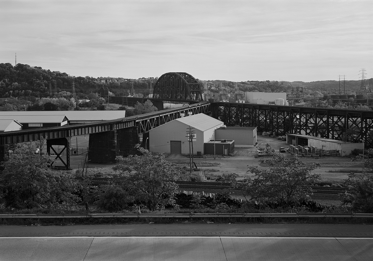 View of Ohio River Connecting Bridge from California Ave in Woods Run Section of Pittsburgh on the North Bank of the Ohio River. Note the diverging trestle,the left leading to Island Ave Yard and right to the Fort Wayne Line. The Mainline is just visible below Ohio River Boulevard in the foreground. The first large through span crosses the Main Channel and measures 508' while the further spans the Back Channel and measures 406', all maintaining a clearance of 68' to the Ohio River below.