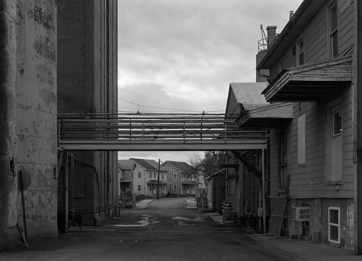 Former Milling Complex of the Wheatena Company, ConAgra and finally Homestat Farms Ltd located off Second Street in Highspire Pennsylvania. The facility straddles Jury St, in this view looking West. To the right (North) is the milling buildings and offices, the left (South) are the storage silos. The dwellings in the background are typical of the area, resembling company homes from the nearby former Bethlehem Steel Steelton Plant. If one looks carefully there is a former Chessie Covered hopper tucked away to the left of the grade crossing in the center foreground.